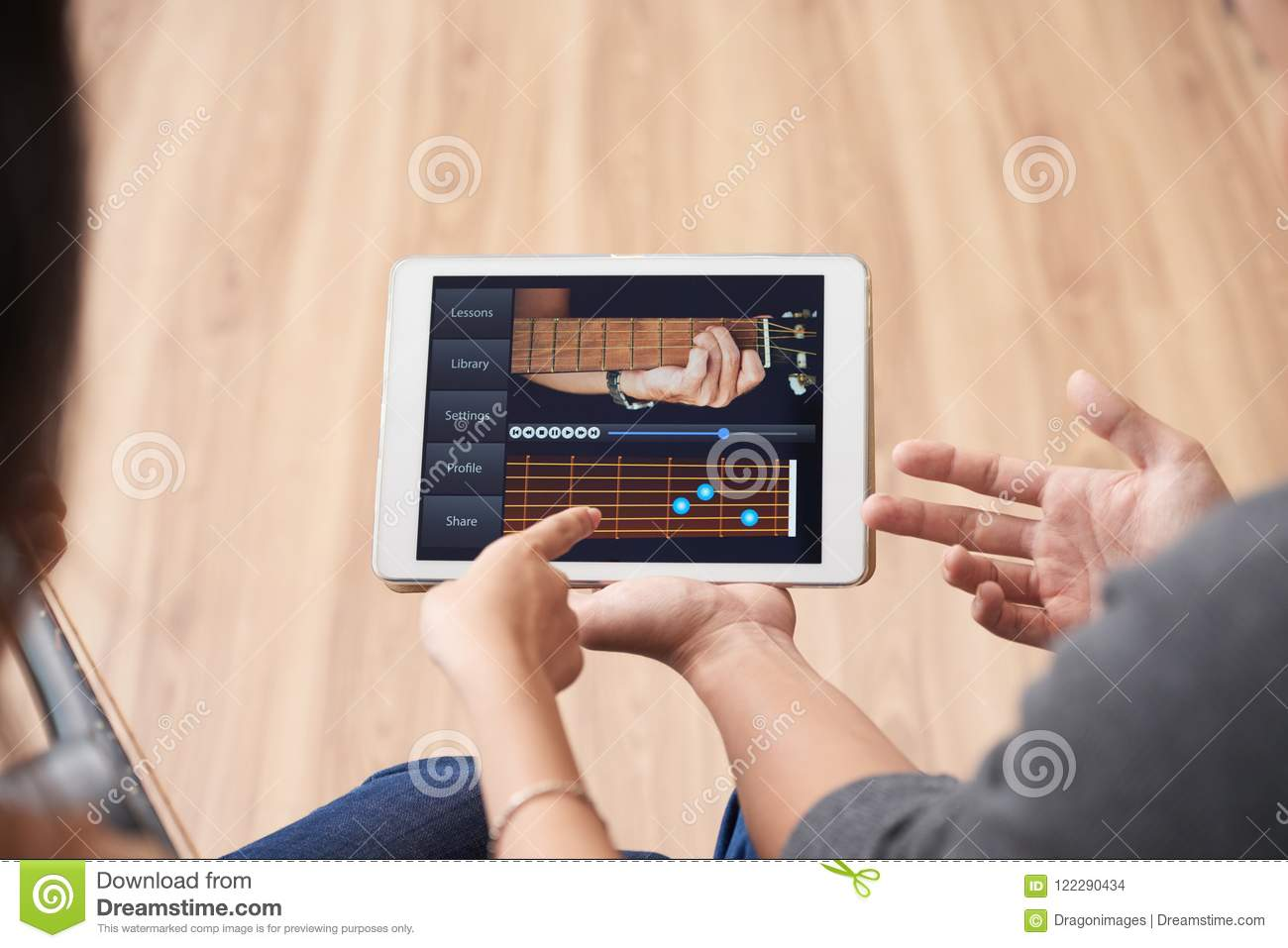 Couple watching guitar video lesson on tablet