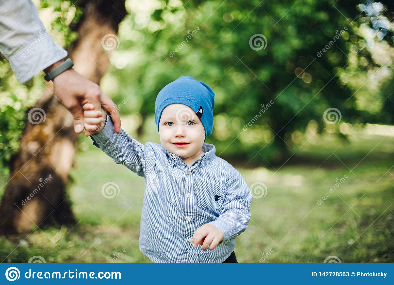 Crop of father holding by hand baby boy, walking in summer park. Little boy in blue cap wearing in checked shirt smiling and having fun outside in nature stock photos
