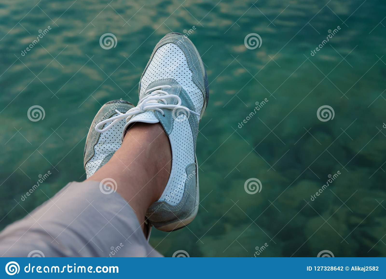 Crop view of female feet on seashore background. Personal point
