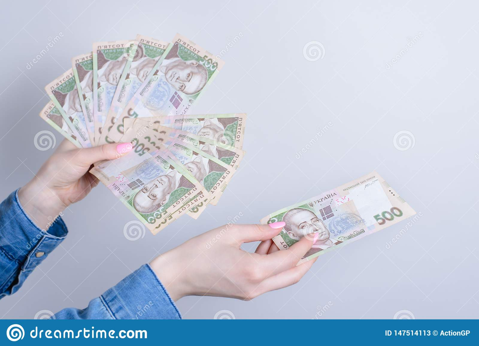 Cropped close up photo of lady`s hands holding pile stack of money gicing to copy space  grey background