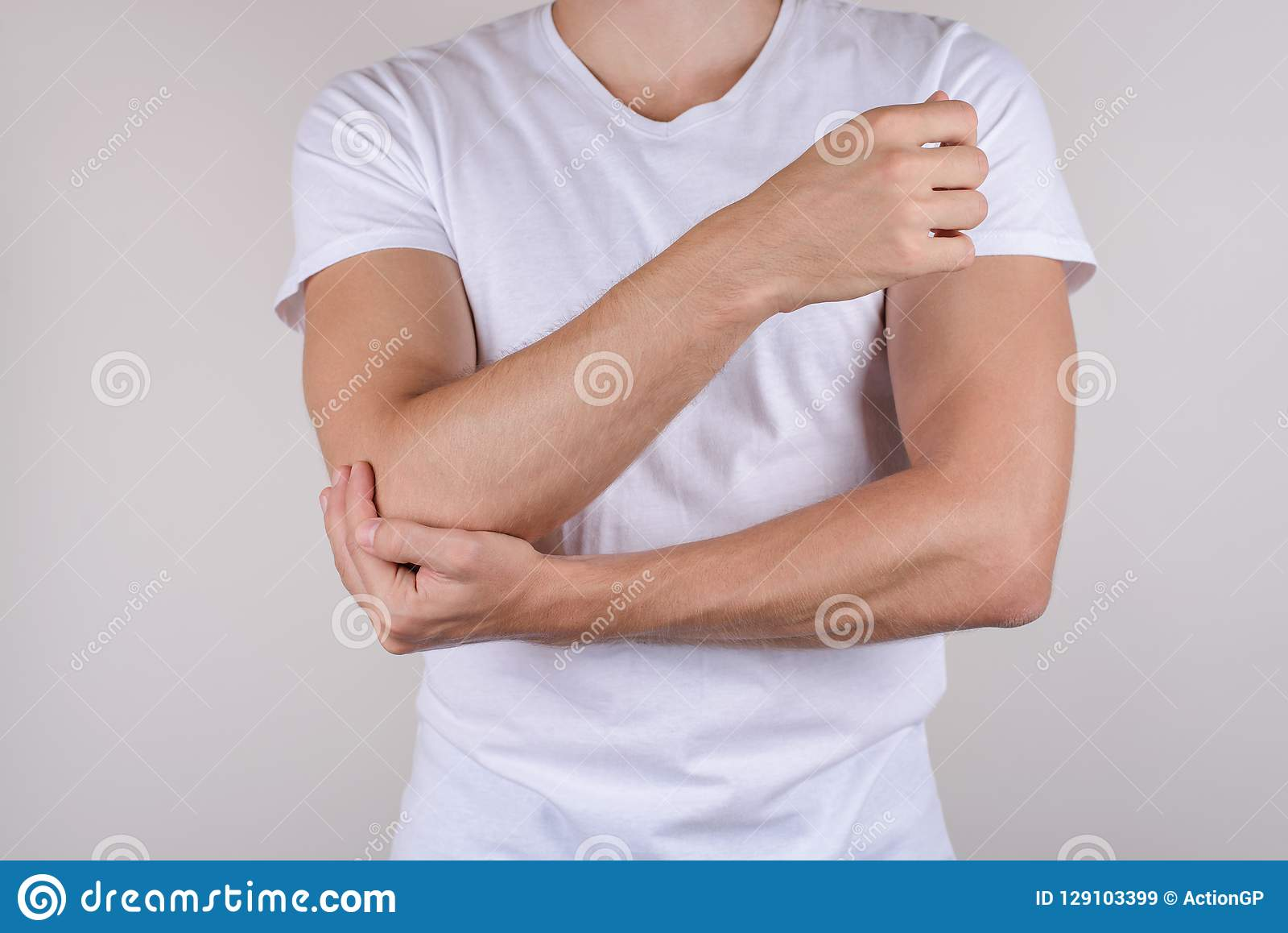 Cropped close up photo portrait of unhappy upset sad guy holding touching painful elbow wearing white t-shirt isolated grey backgr