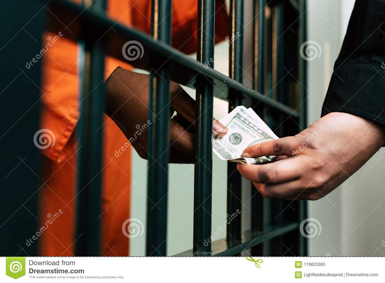 cropped image of african american prisoner giving money to prison guard