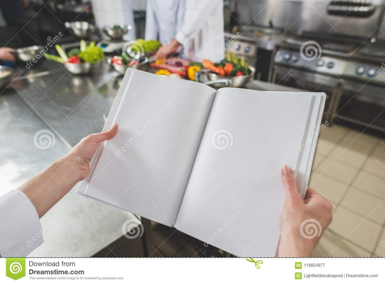 Cropped Image Of Chef Holding Open Recipe Book Stock Image