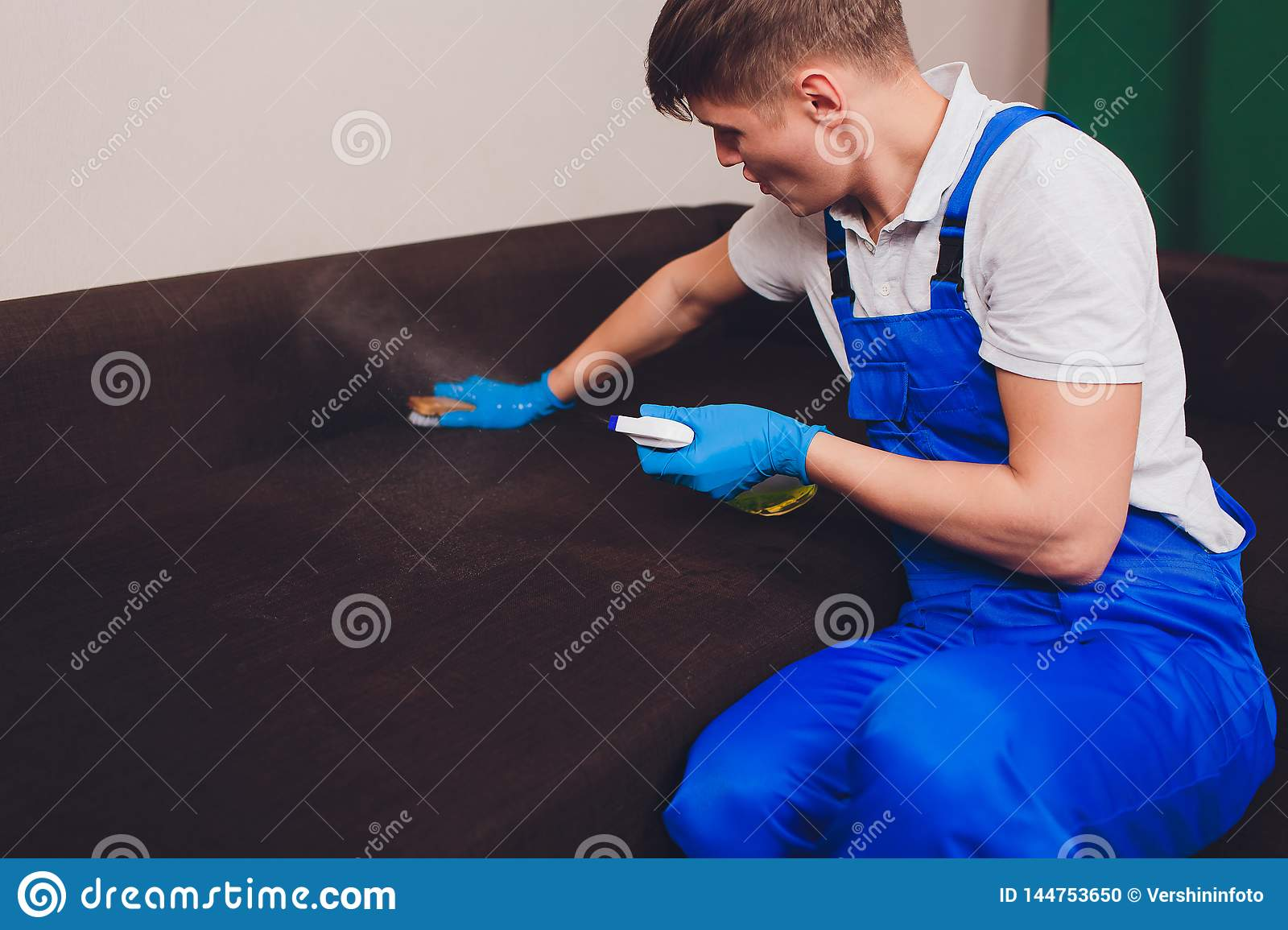 Cropped image. Cleaning concept. Male hand in blue protective gloves cleaning sofa couch in the room.