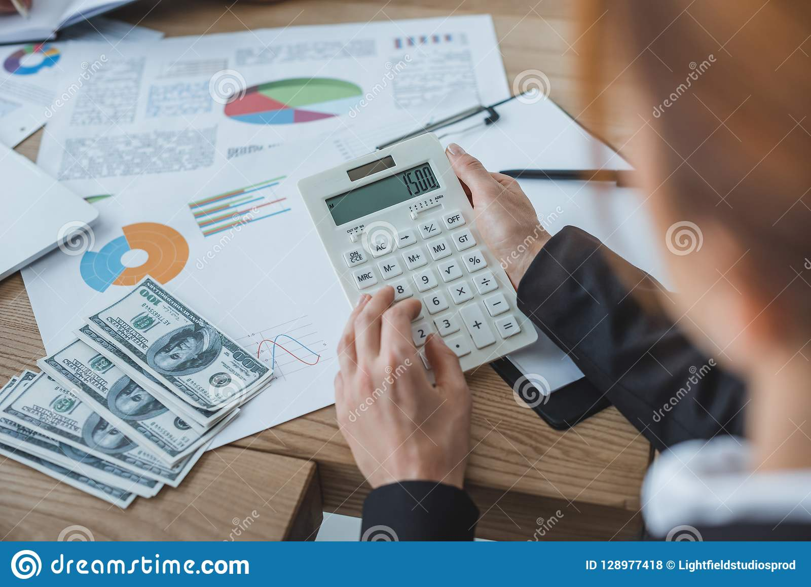cropped image of financier using calculator at work