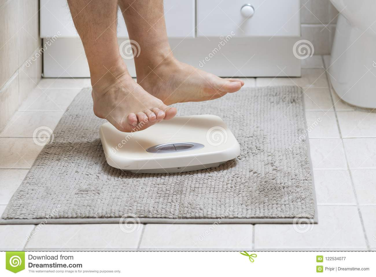 Cropped image of man feet jumping on weigh scale
