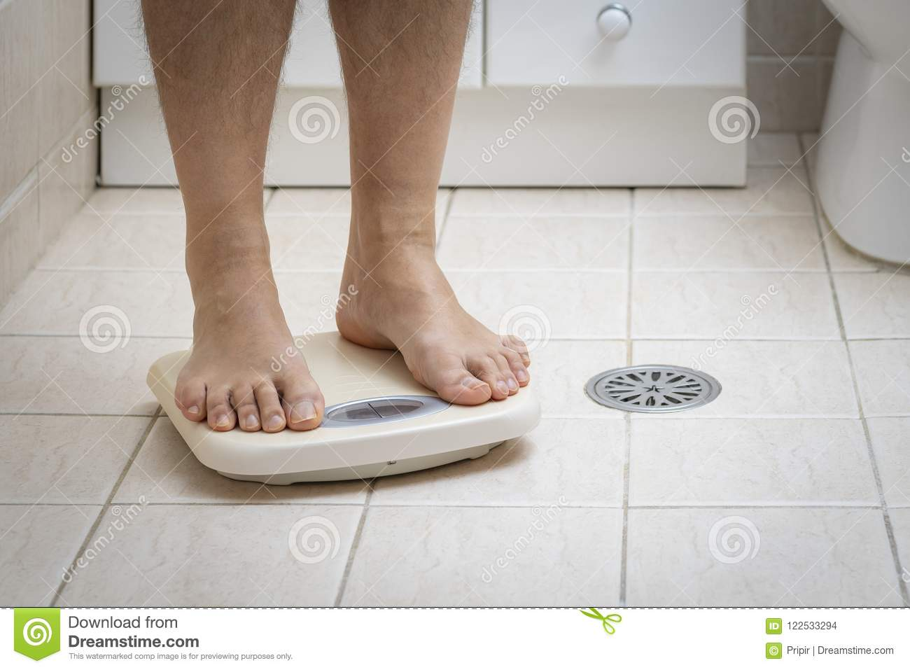 Cropped image of man feet standing on weigh scale