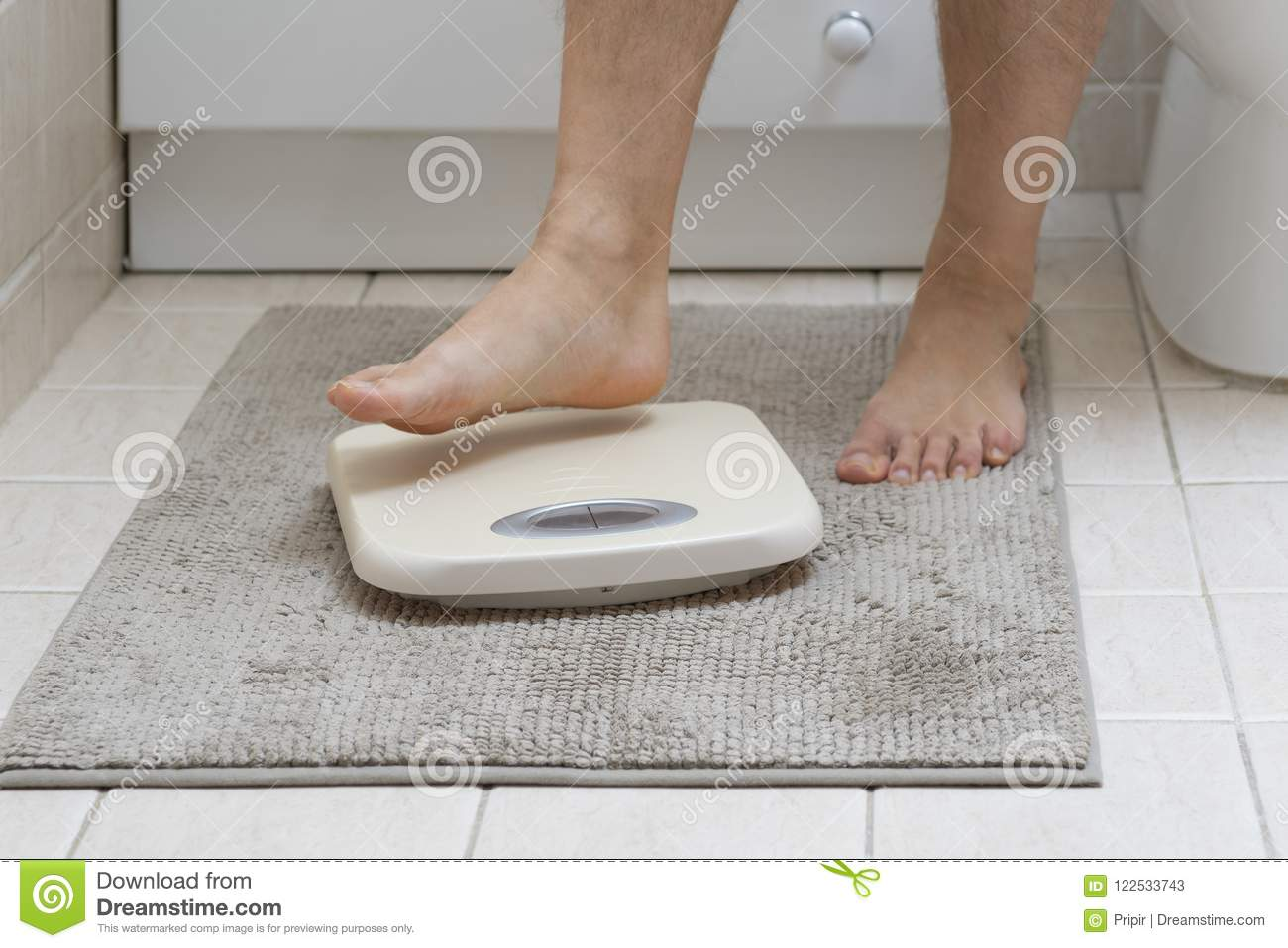 Cropped image of man feet stepping on weigh scale
