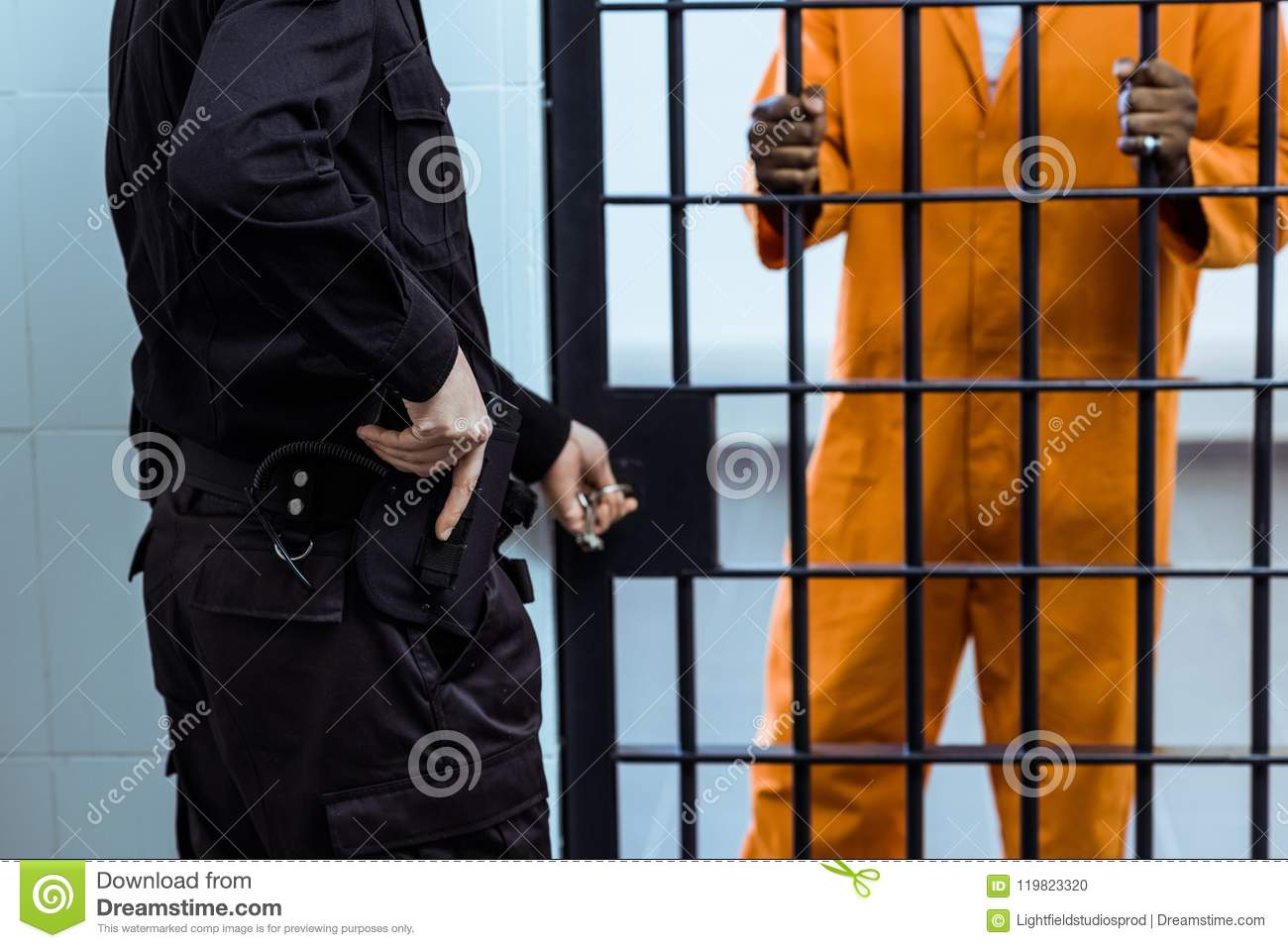cropped image of prison guard putting hand on gun