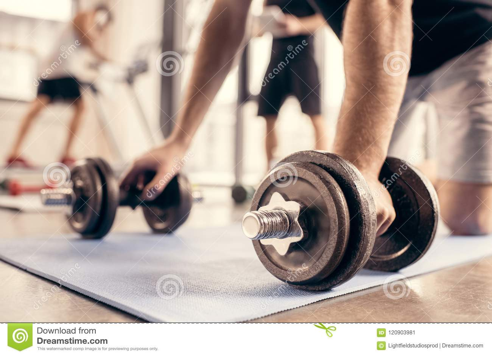 cropped image of sportsman preparing doing push ups on dumbbells