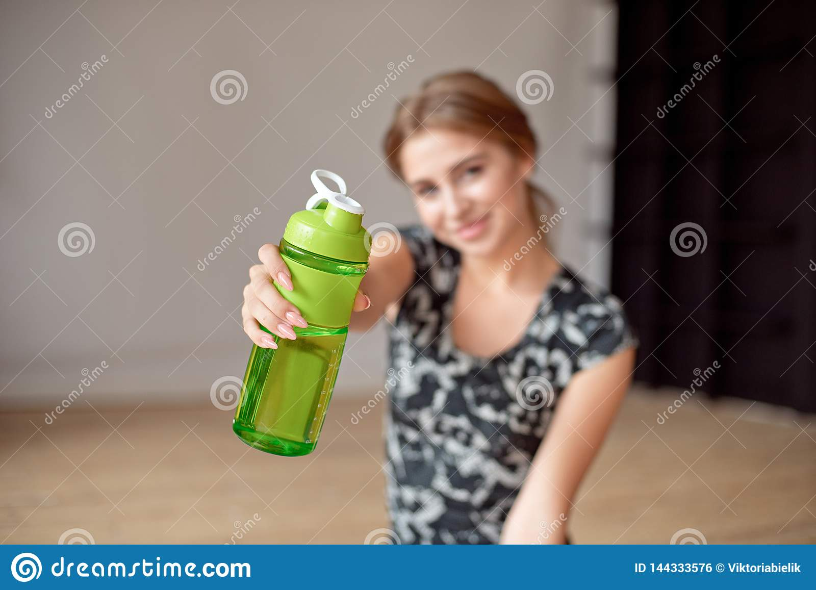 Cropped image of sporty woman holding bottle of water.