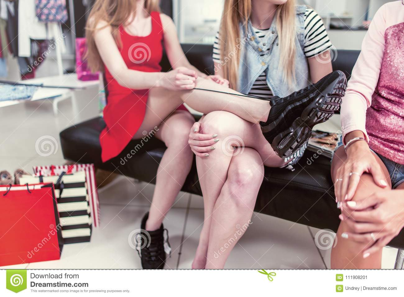 Cropped image of teen girls sitting on bench relaxing after shopping in clothing store. Young stylish woman tying up new