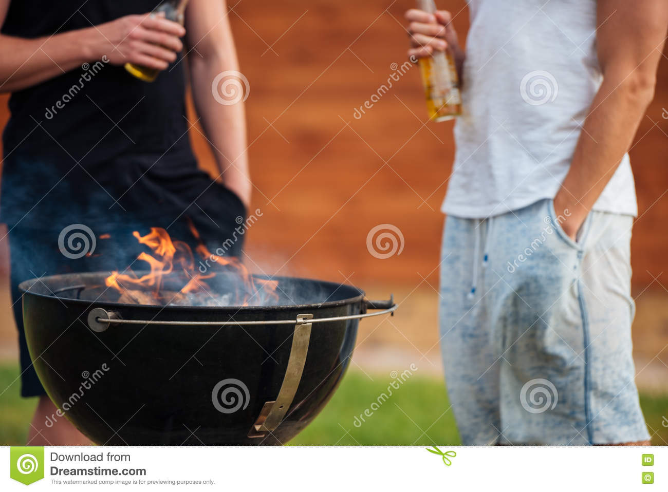 Cropped image of two men holding beer bottles while barbecue