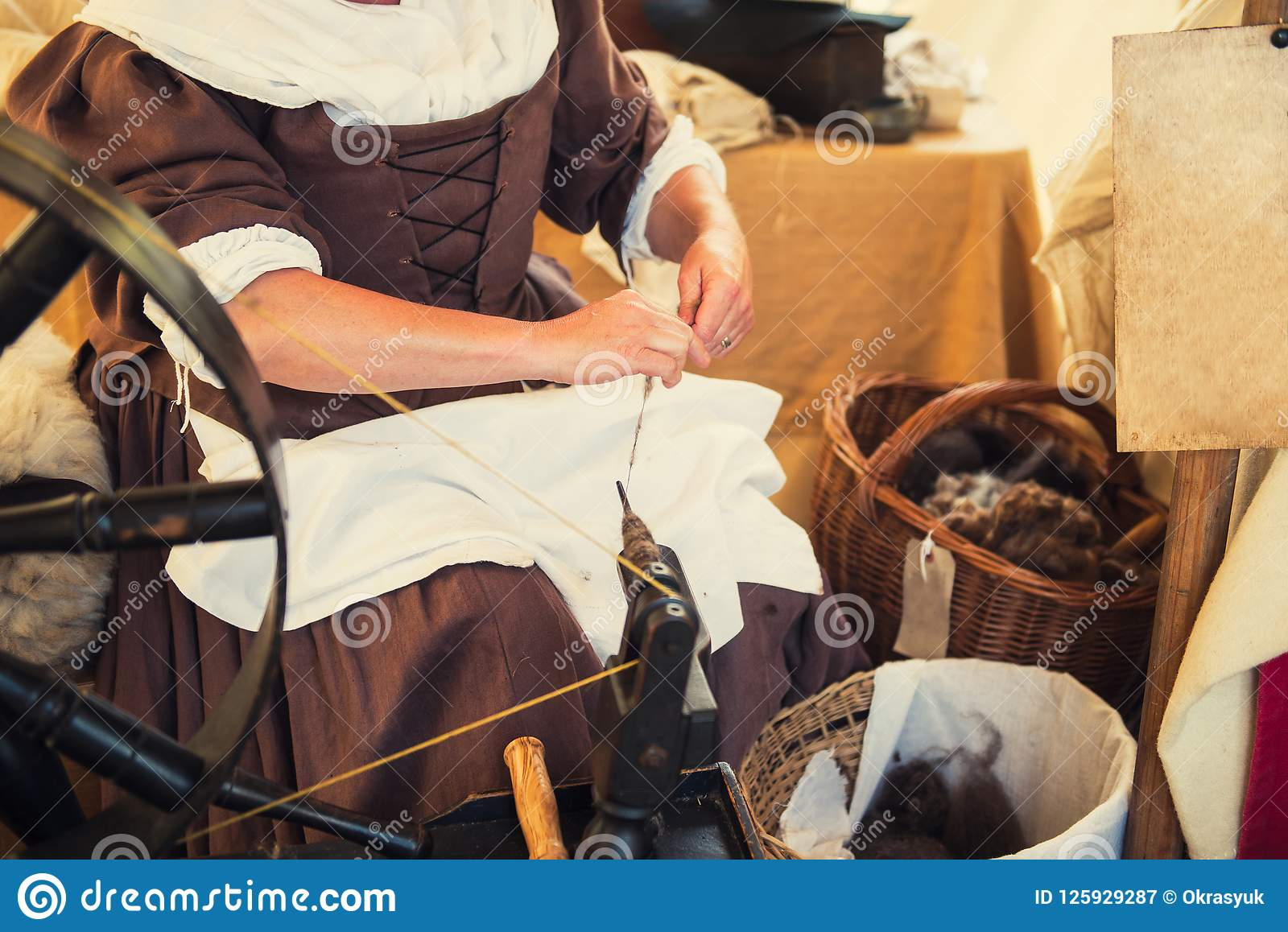 Cropped image of weaver in Middle Agesl clothes make yarn on spinning wheel. Medieval crafts, occupation. The concept of historica