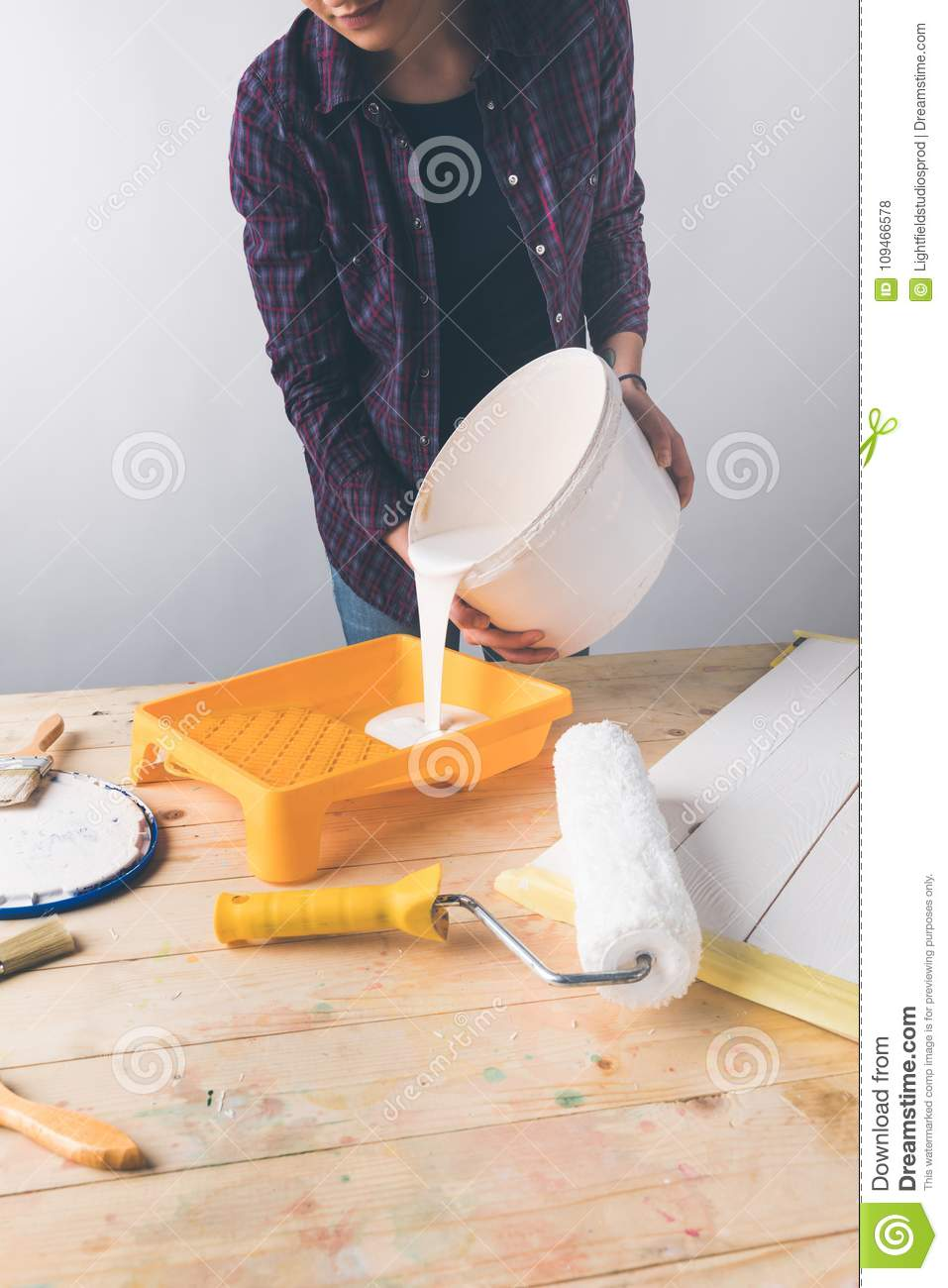 Woman pouring white paint into plastic tray