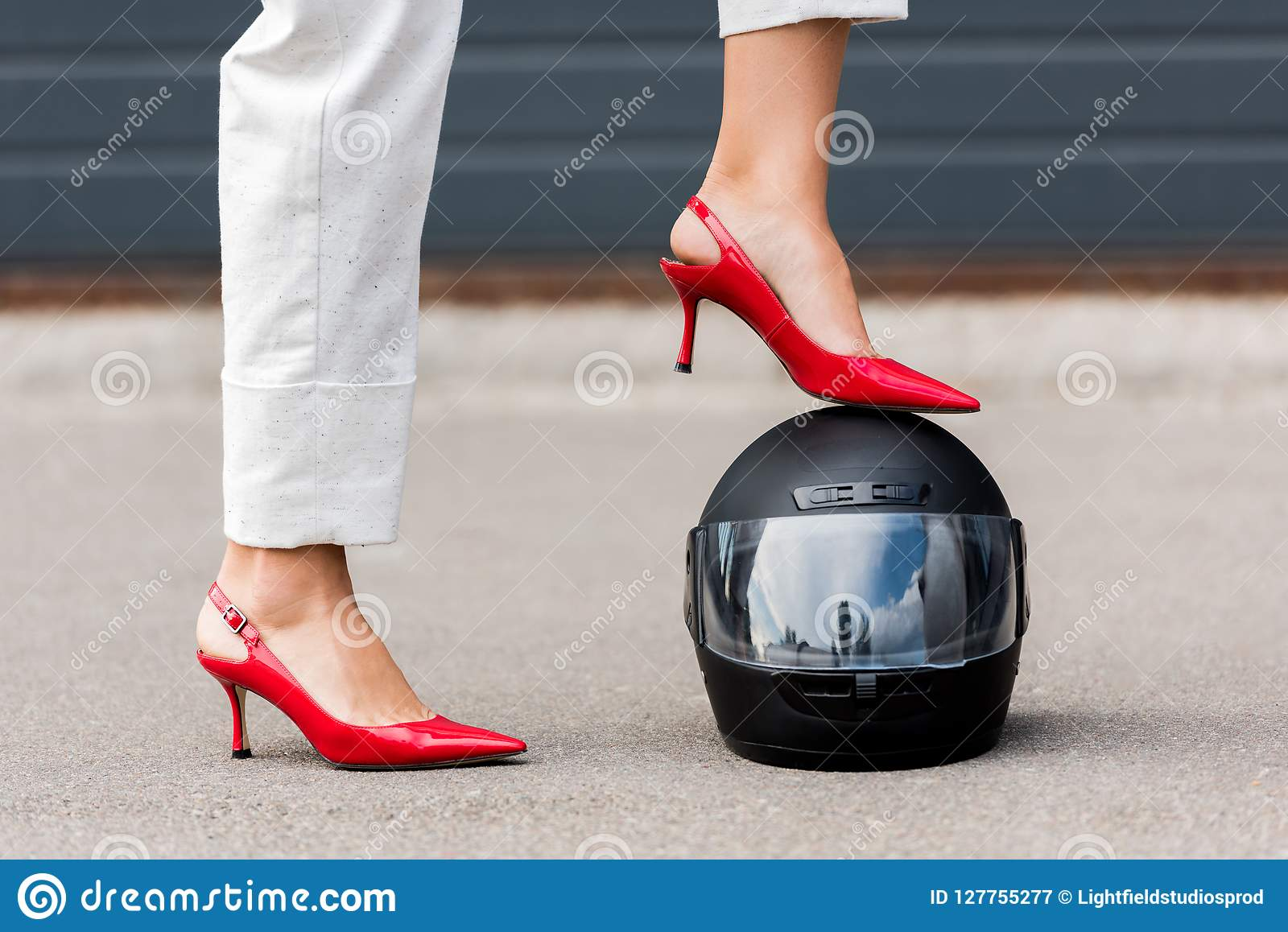 cropped image of woman in red high heels putting leg on motorcycle helmet on street
