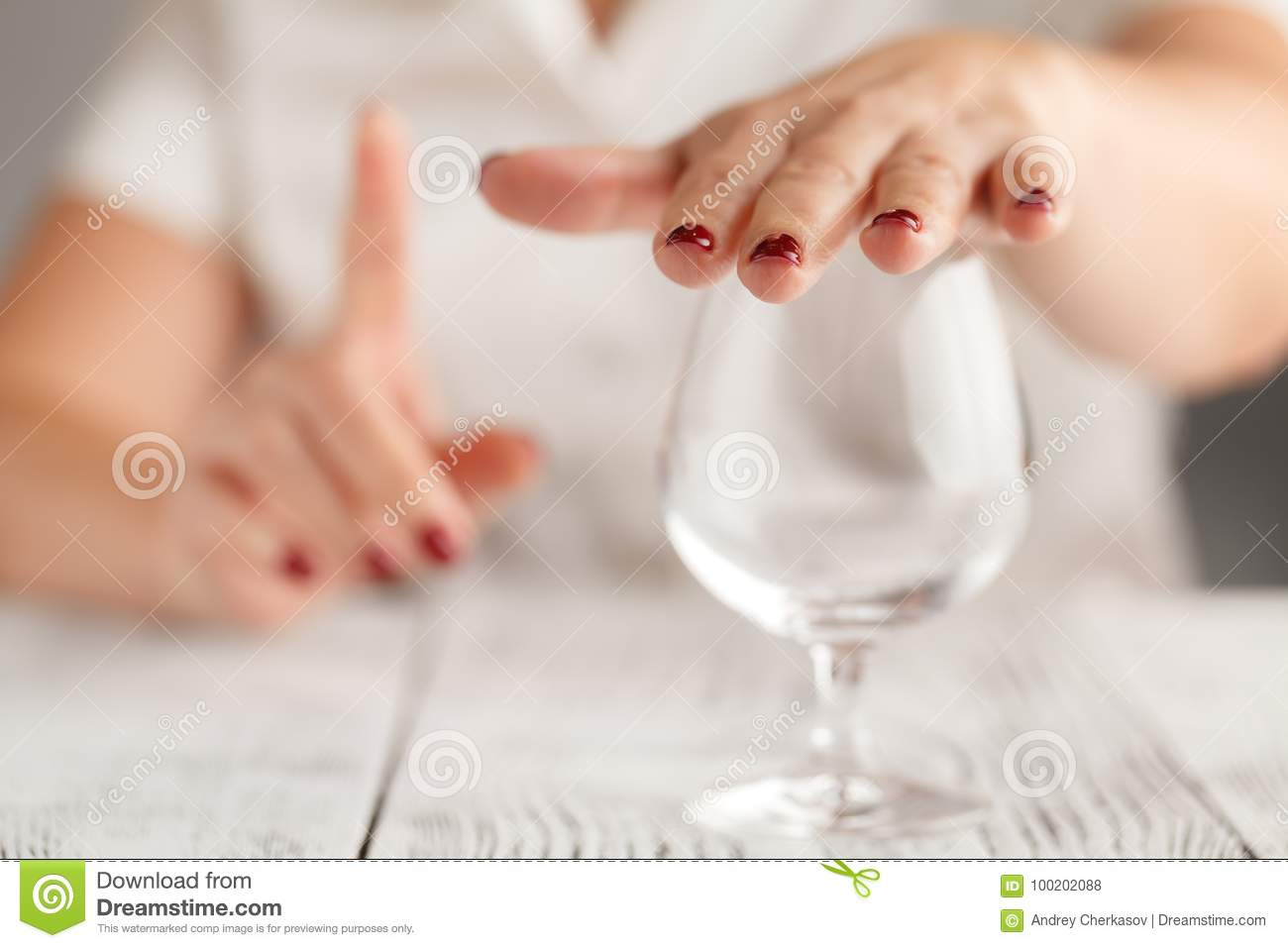 Cropped image of woman showing stop gesture and refusing to drink