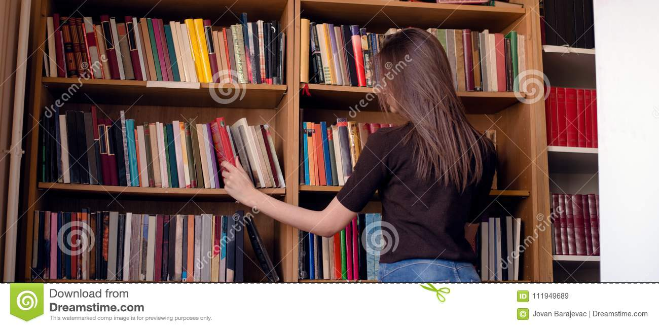 Download Cropped Image Of Woman Taking Book From Bookshelf Stock