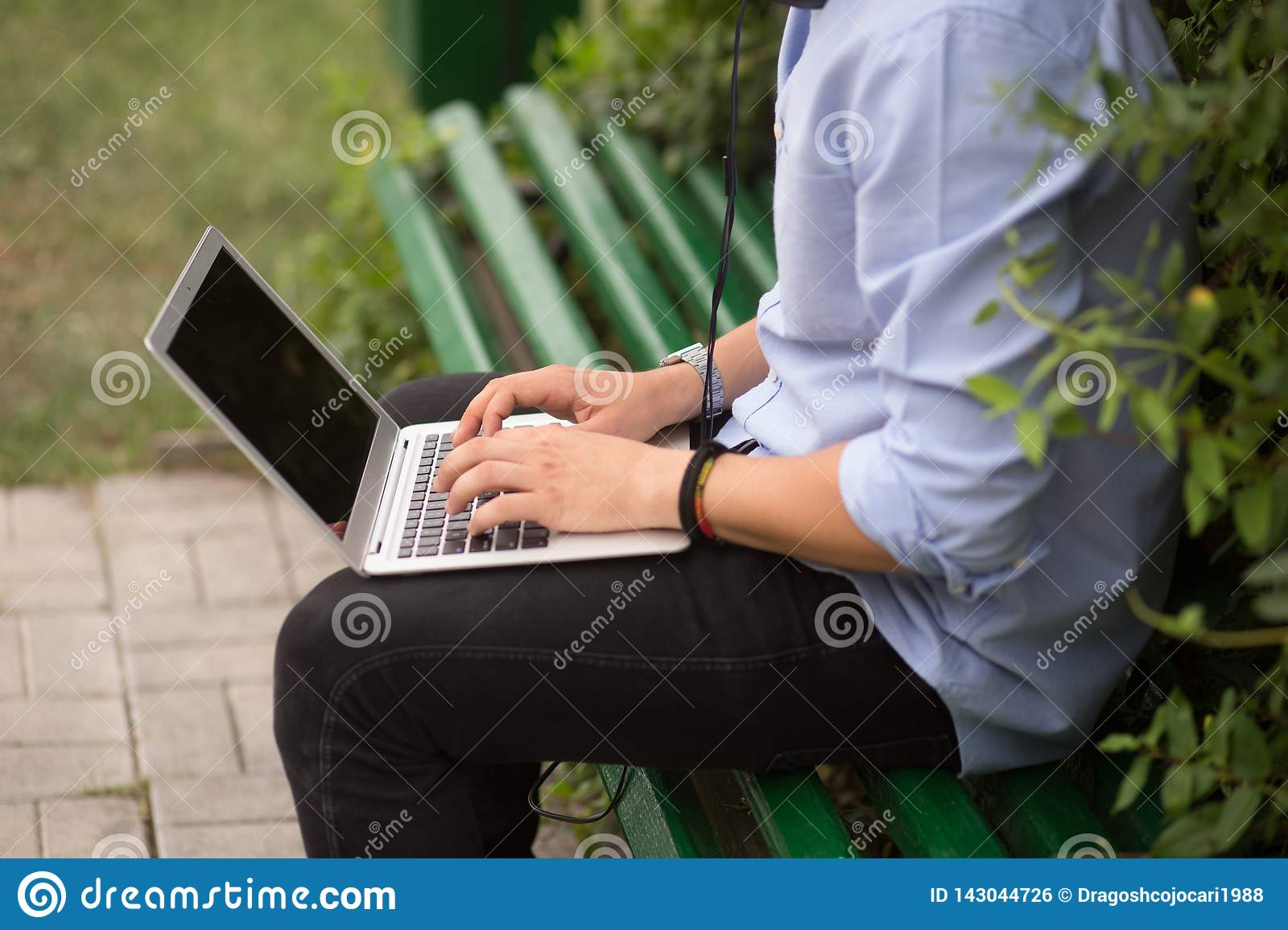 Cropped image of young man sitting at on the bench in the park, using a laptop.