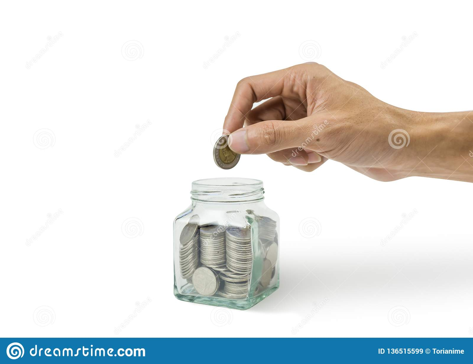 A cropped of man hand holding coin over many coins in glass jar on white background