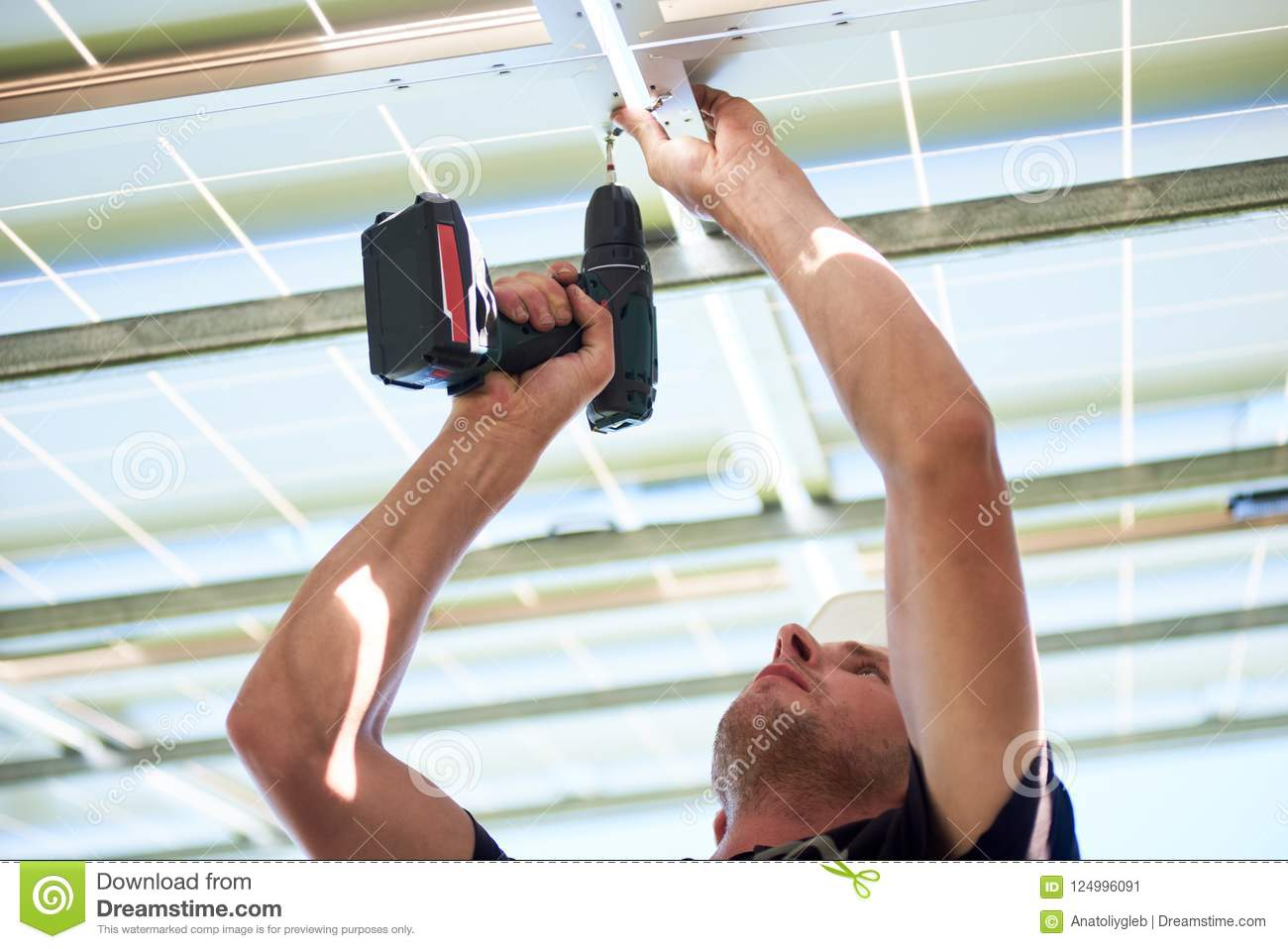 Cropped photo of worker using drill by solar panels mounting.