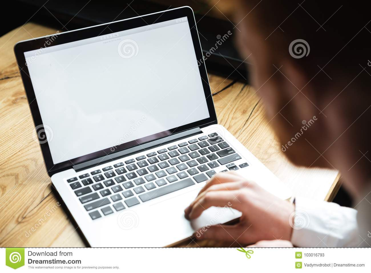 Cropped photo of young man using laptop on wooden table