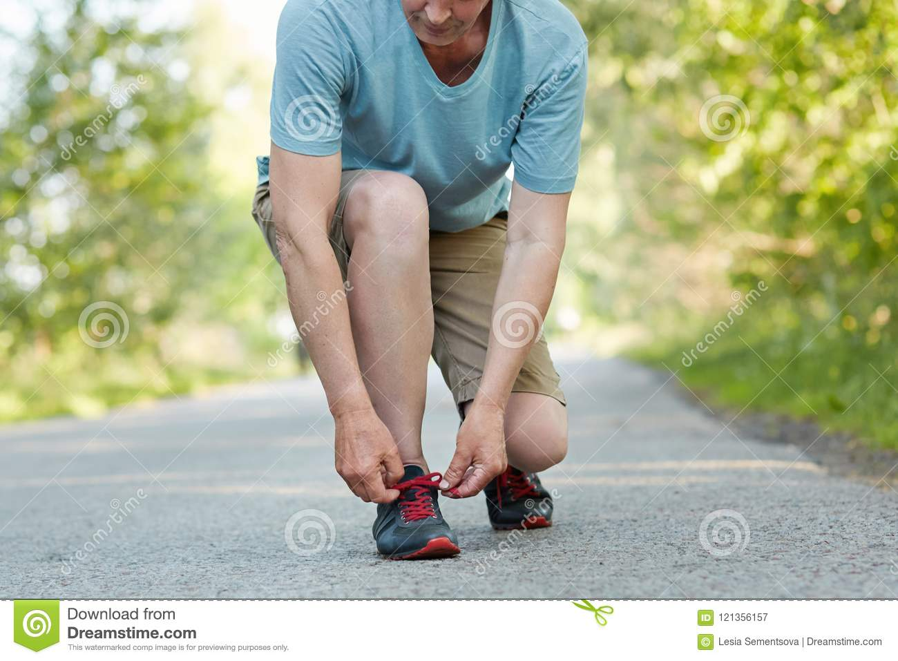 Cropped shot of elderly male athlete ties shoelaces, takes rest after jogging exercise, wears sportswear, poses outdoor. Man runne