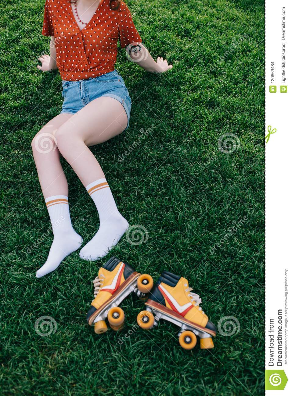 Girl with skateboard lying on grass — Stock Photo