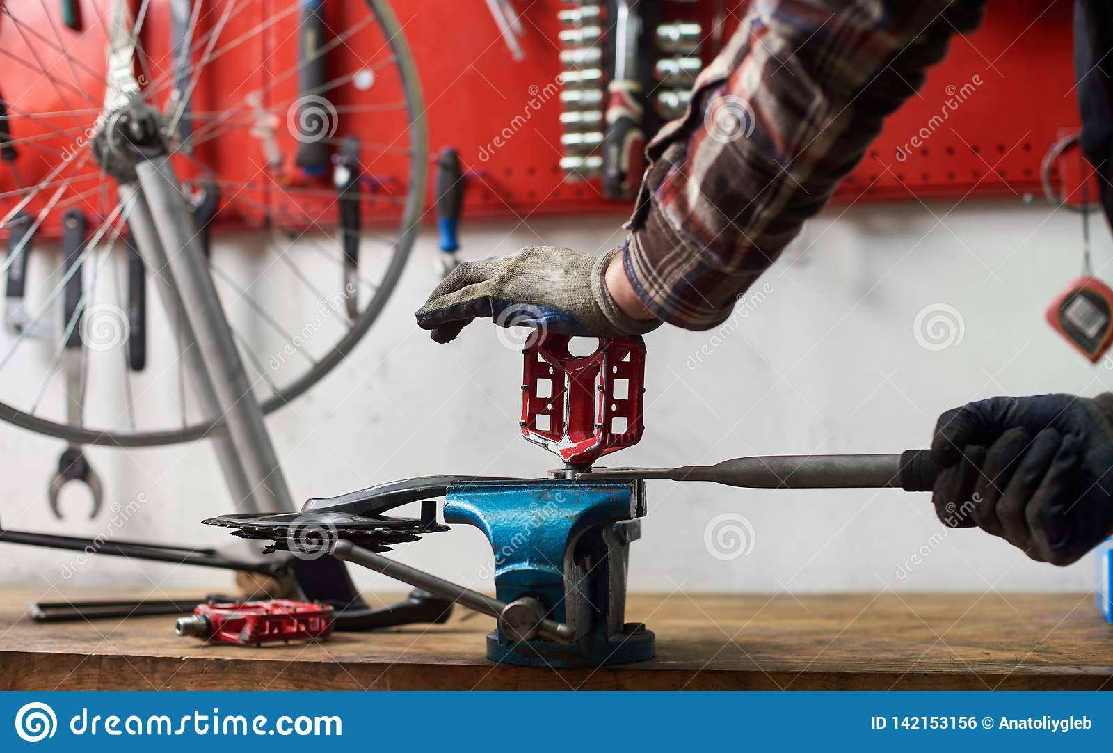 Male Mechanic Working In Bicycle Repair Shop Using Tools
