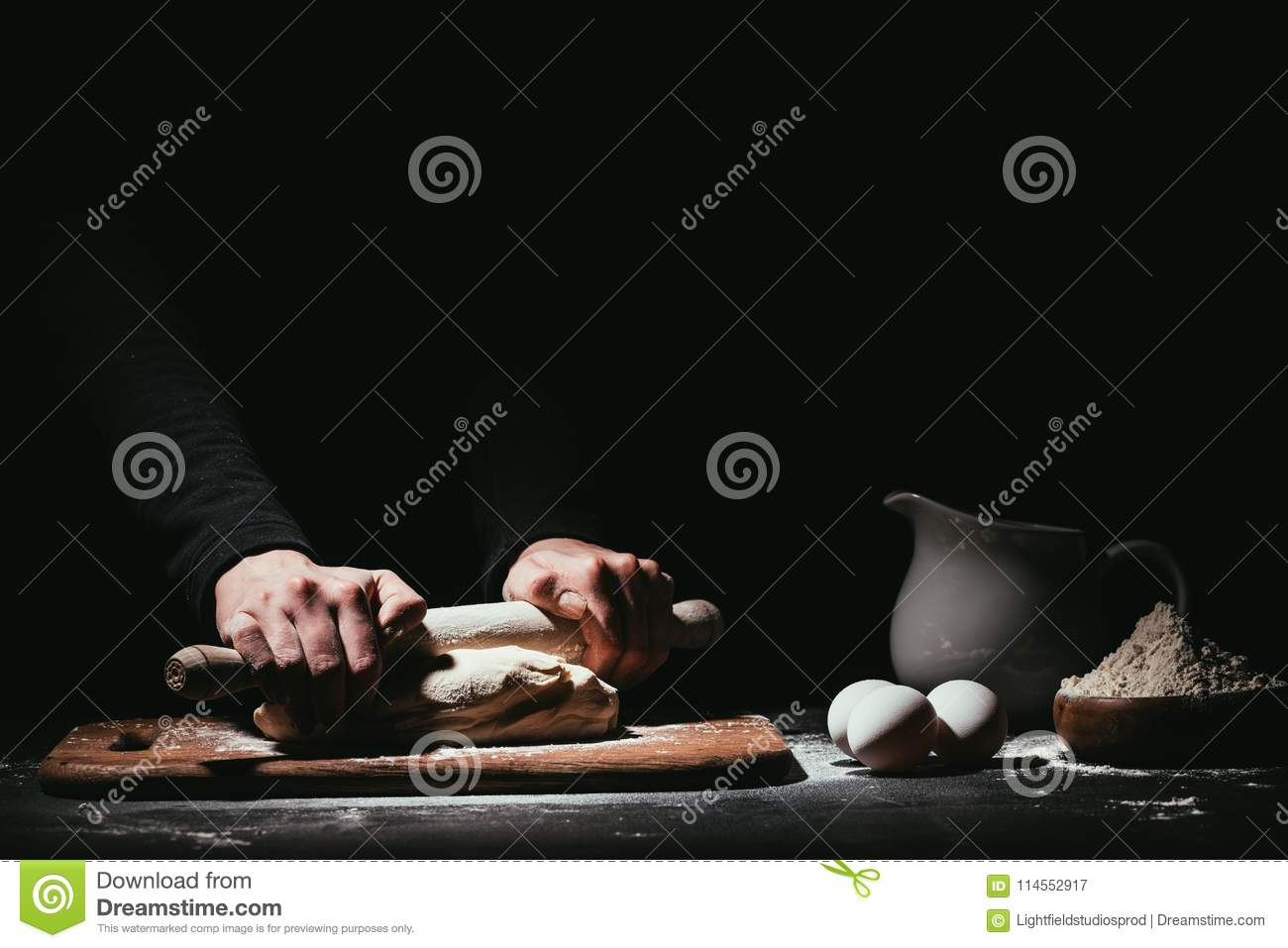 cropped shot of person preparing dough with rolling pin