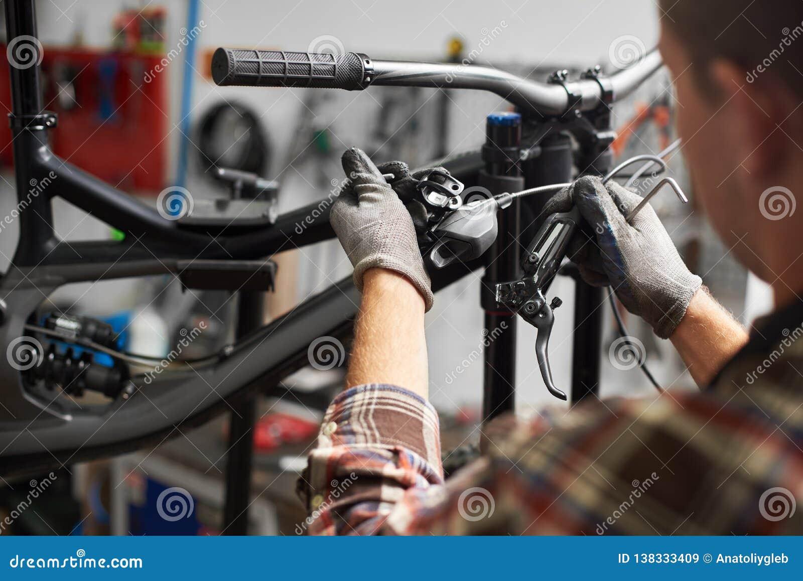 Male Mechanic Working In Bicycle Repair Shop Using Tools