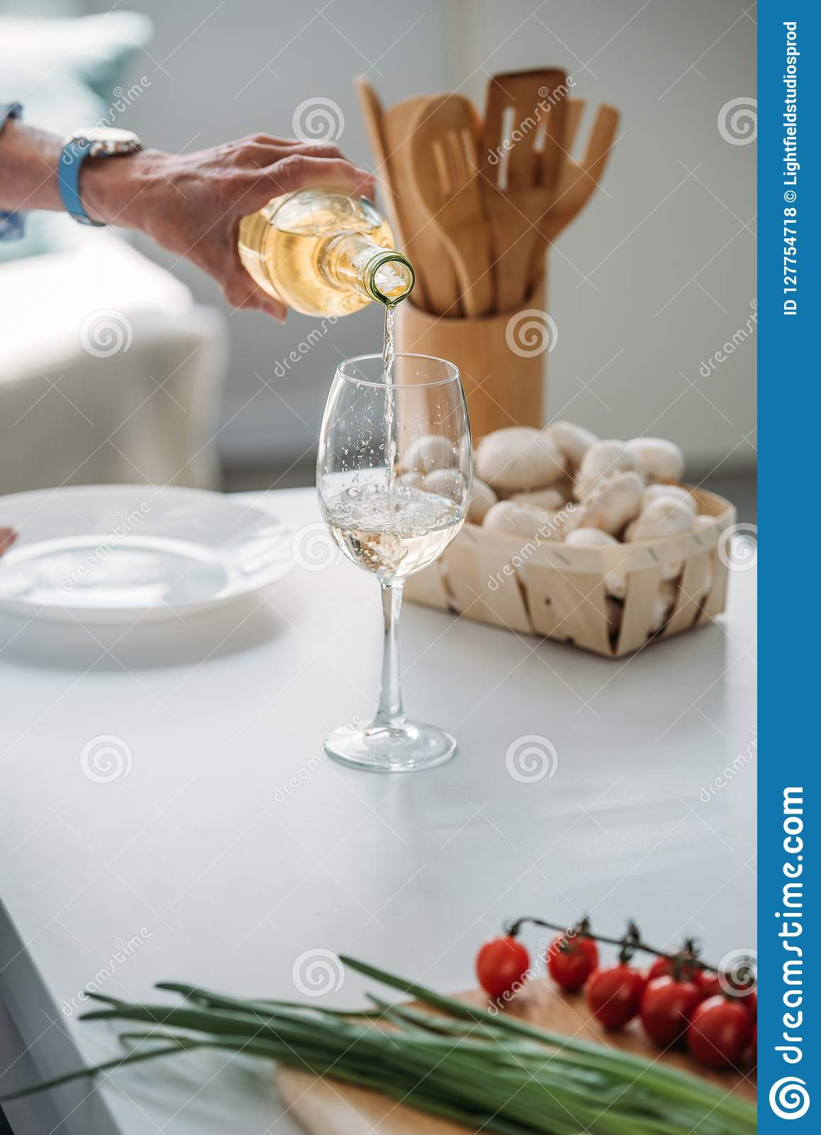 cropped shot of senior woman pouring wine into glass at counter with fresh vegetables in kitchen