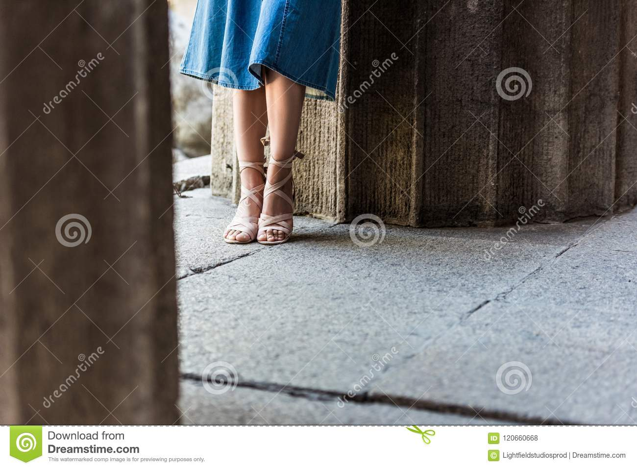 cropped shot of woman in denim skirt and shoes standing