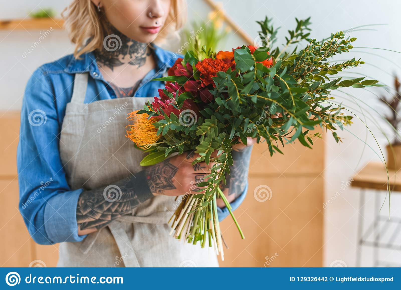 cropped shot of young florist with tattoos holding flower