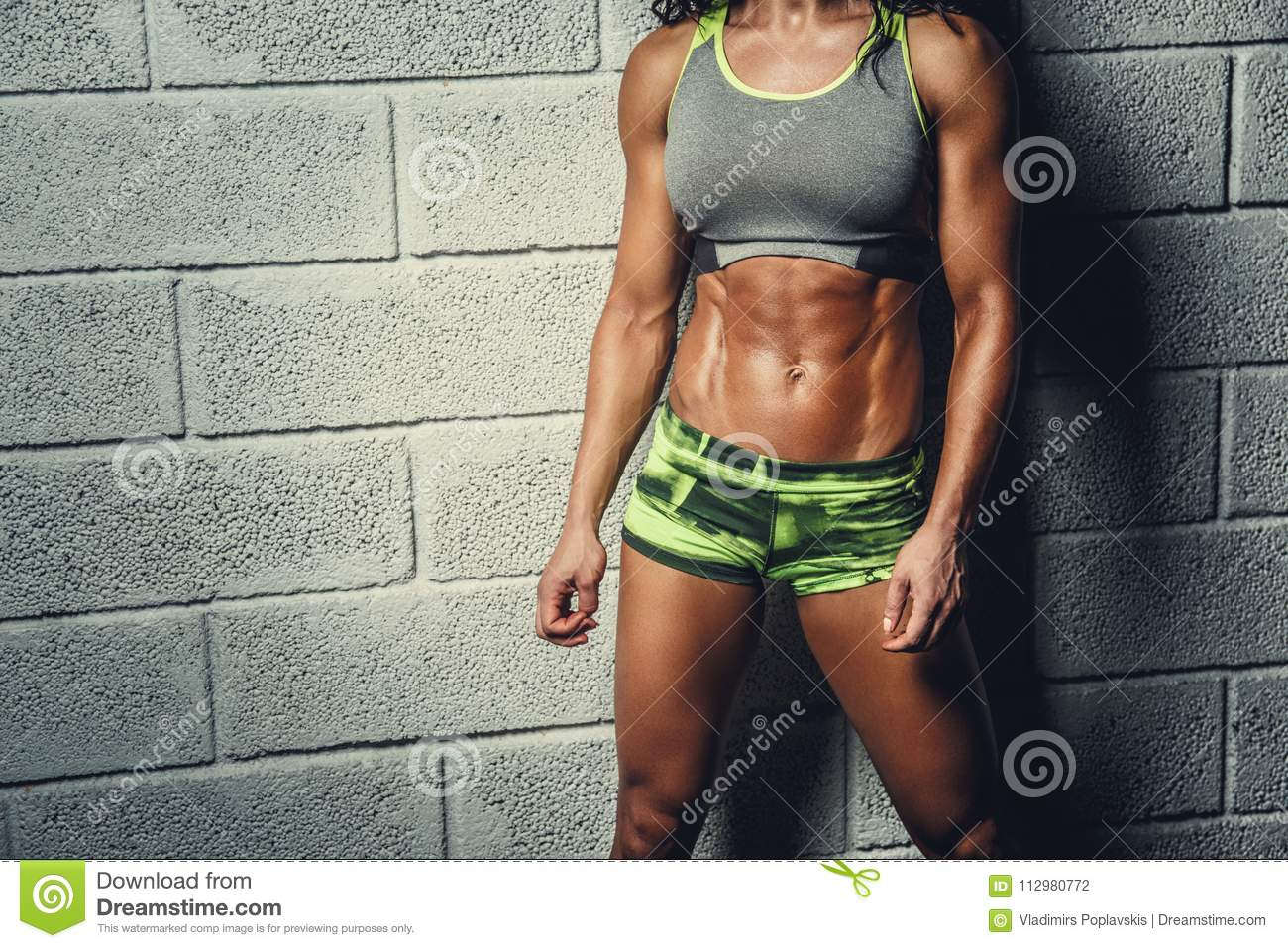 Cropped sporty female`s body over grey background.