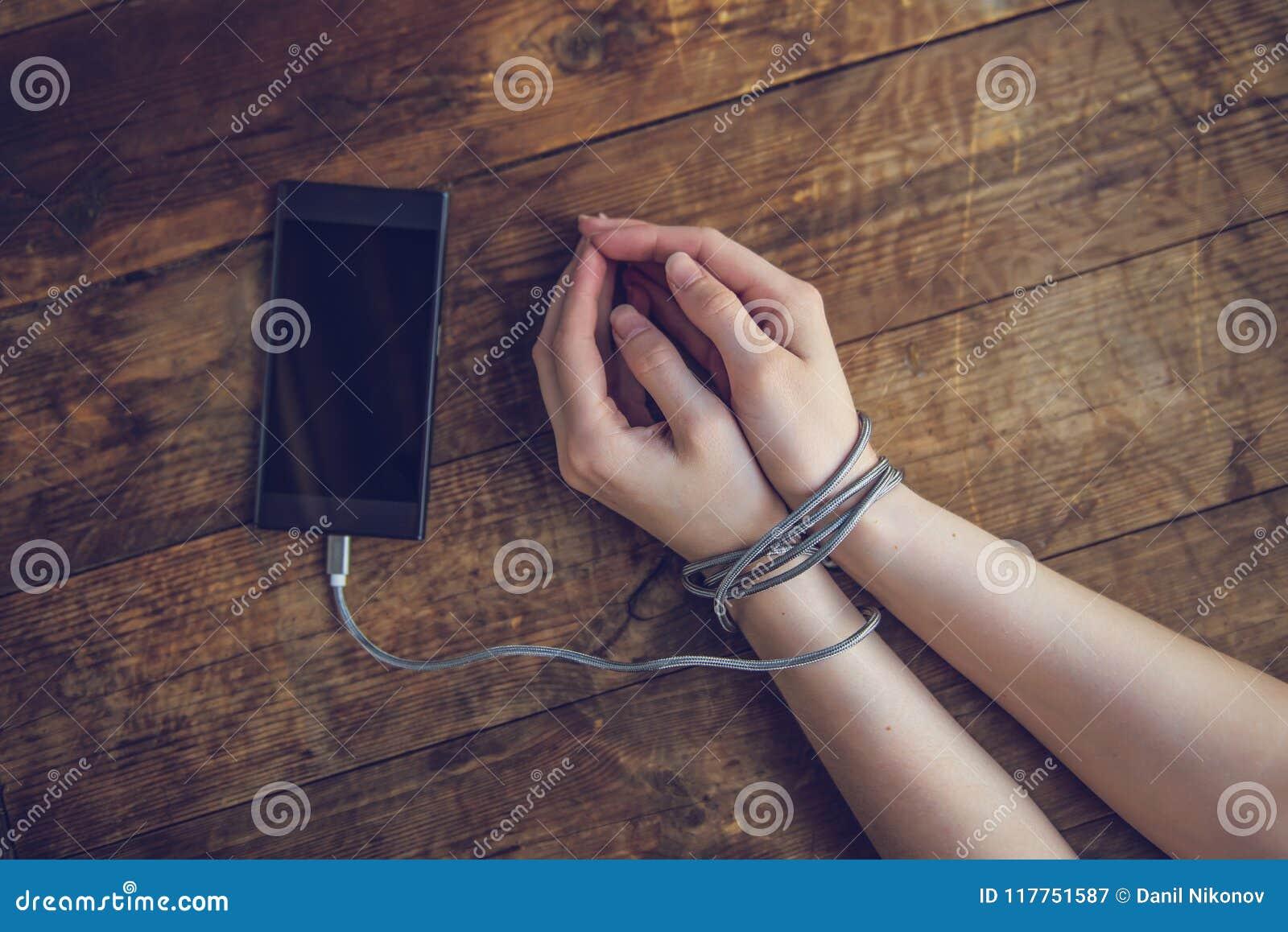 Cropped strzał kobieta z rękami wiązać z smartphone drutem, telefonu nałogu pojęcie