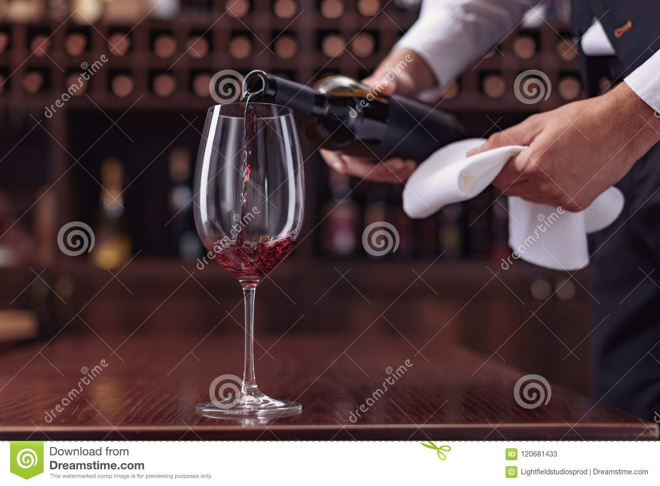 Cropped view sommelier pouring red wine from bottle into glass at table