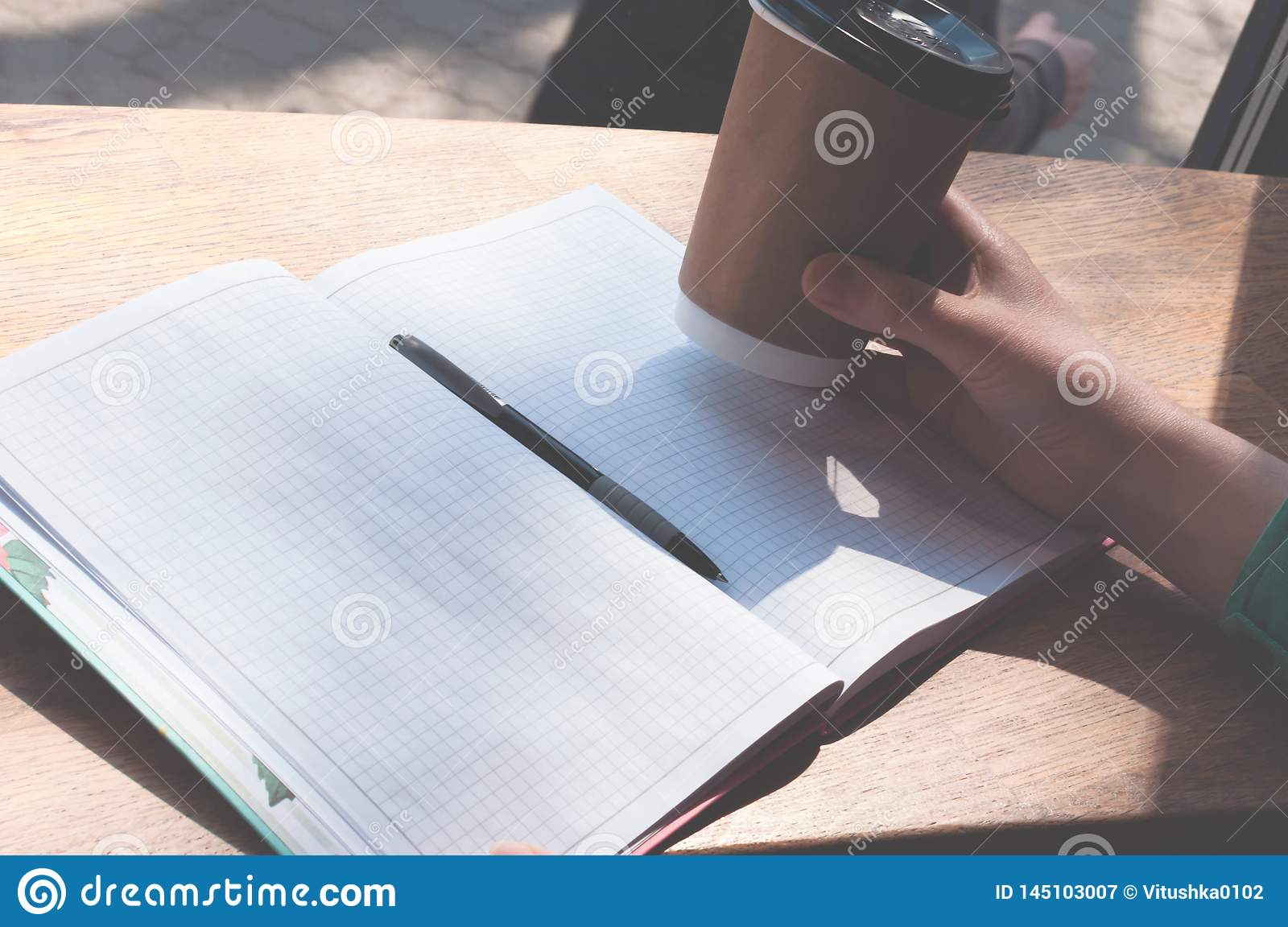 Wooman holding paper cup over pen and notebook with copy space on wooden table in coffee shop