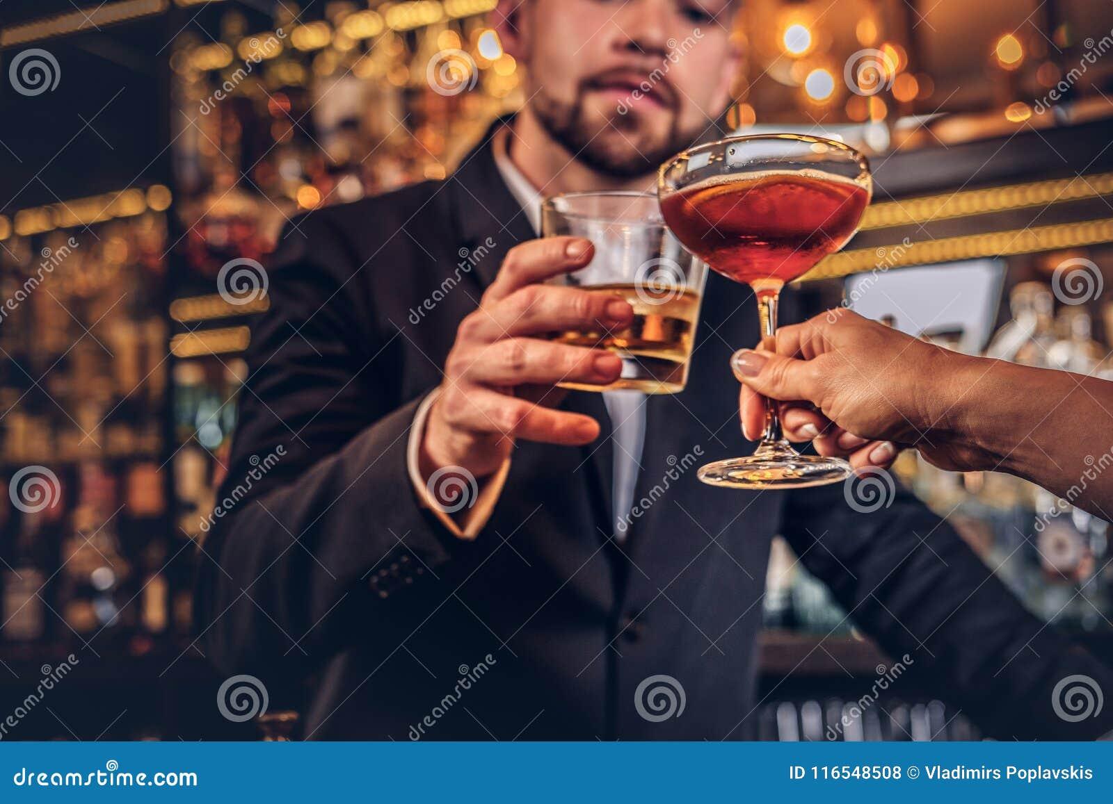 Cropped wizerunek atrakcyjna para wydaje wieczór w romantycznym położeniu, pije wino przy prętowym kontuarem