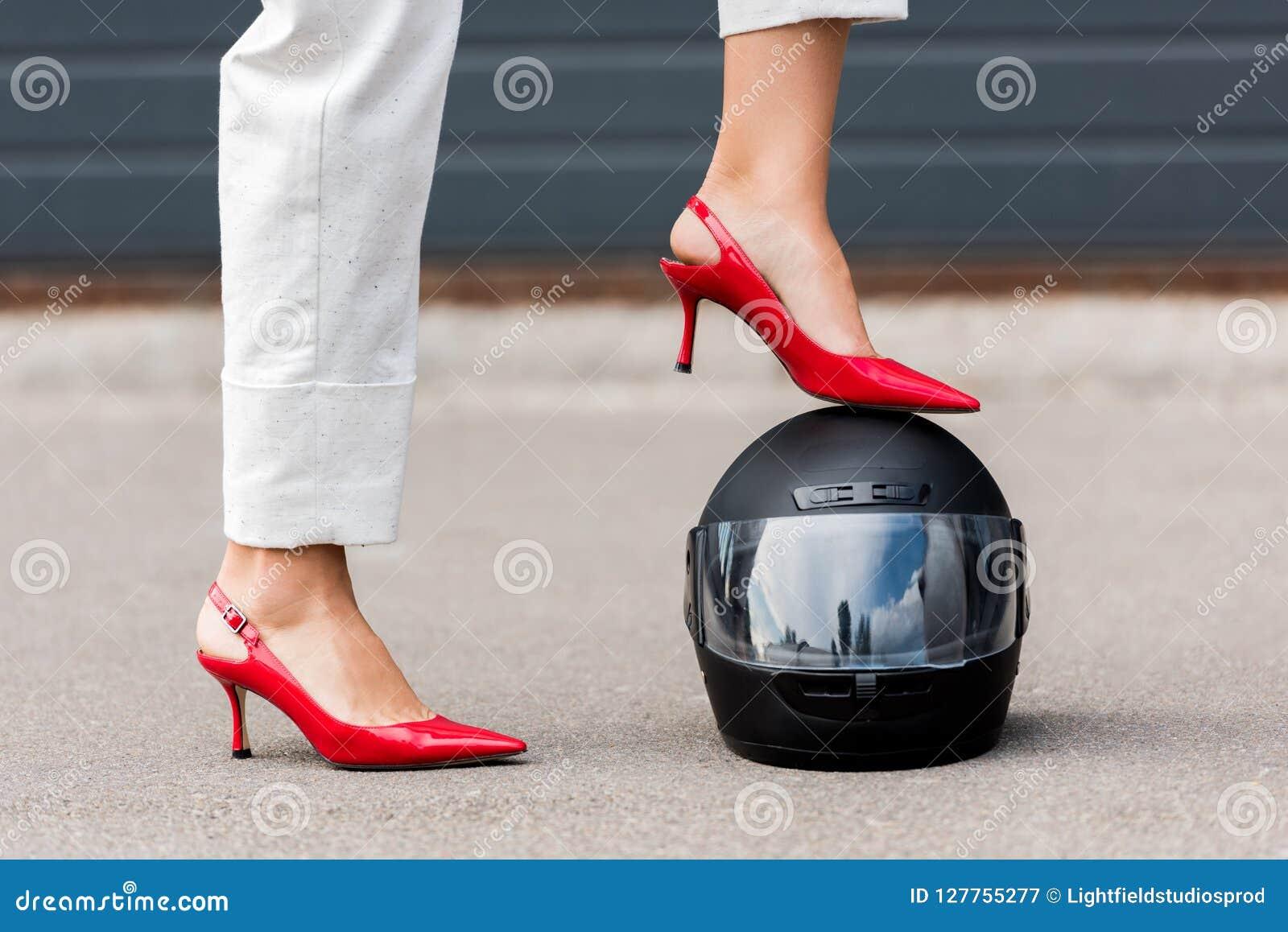 Cropped wizerunek kobieta stawia nogę na motocyklu hełmie na ulicie w czerwonych szpilkach