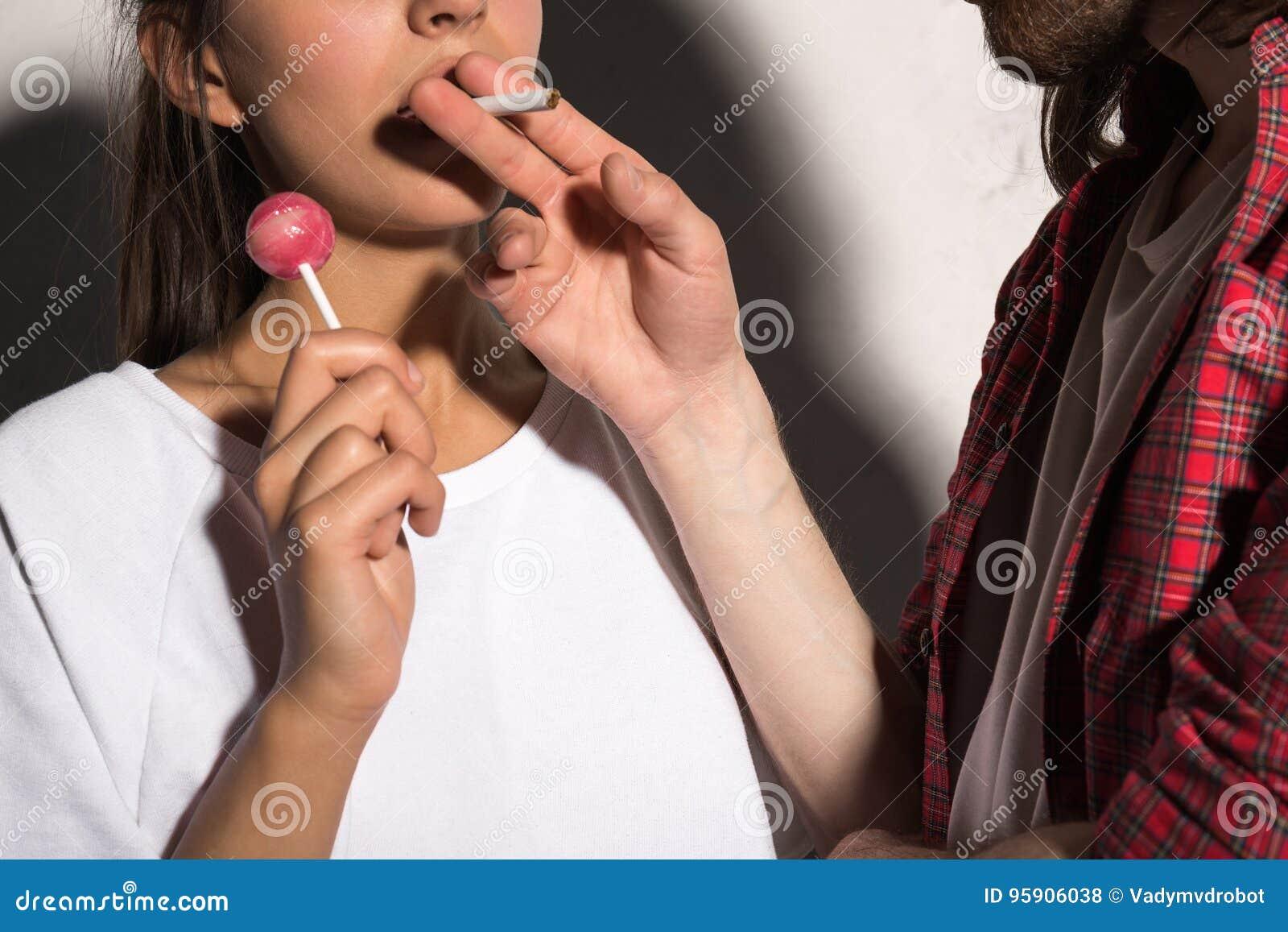 Cropped wizerunek młody modnisia mężczyzna daje papierosowi dziewczyna
