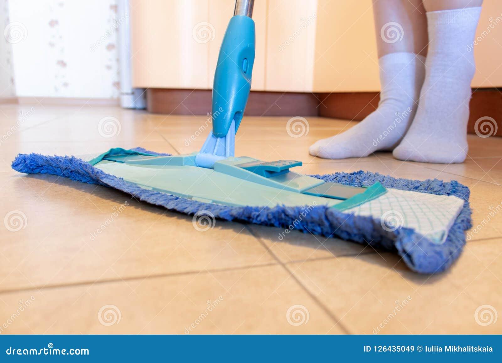Cropped wizerunek piękna młoda kobieta używa błękitnego kwacz w kuchni podczas gdy czyścić podłoga