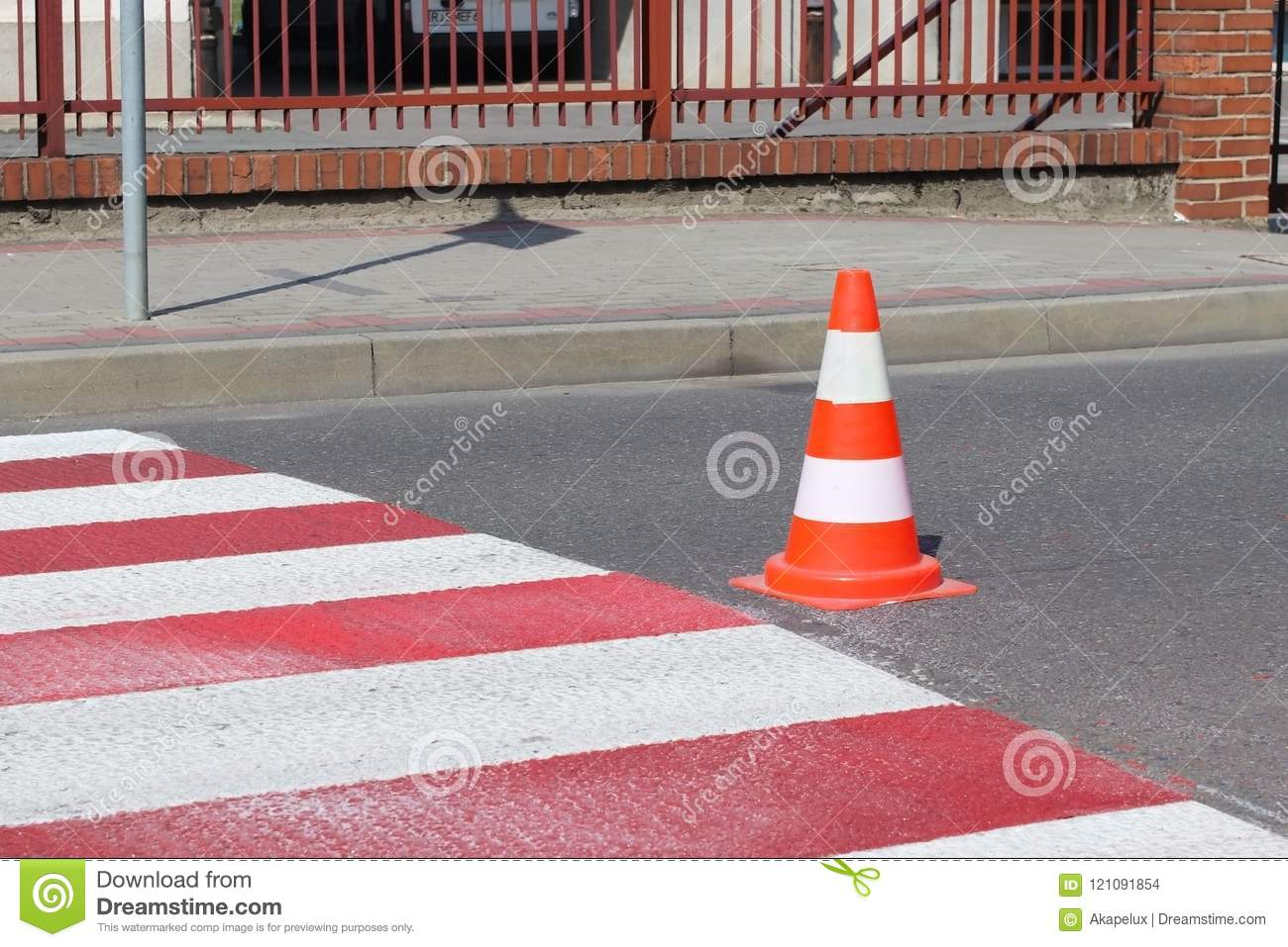 The cross-decorated pedestrian crossing with the still not dried out red. Restriction of traffic by road signs. Update road pedest