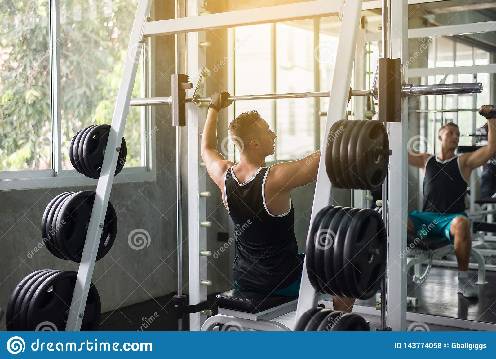 Cross fit body and muscular lifting weight barbell in the gym,Sport man doing exercises training