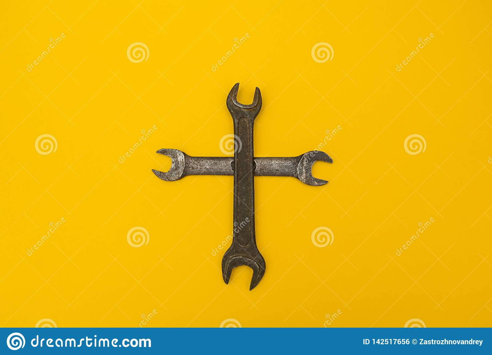 Cross of rusty keys on a yellow background