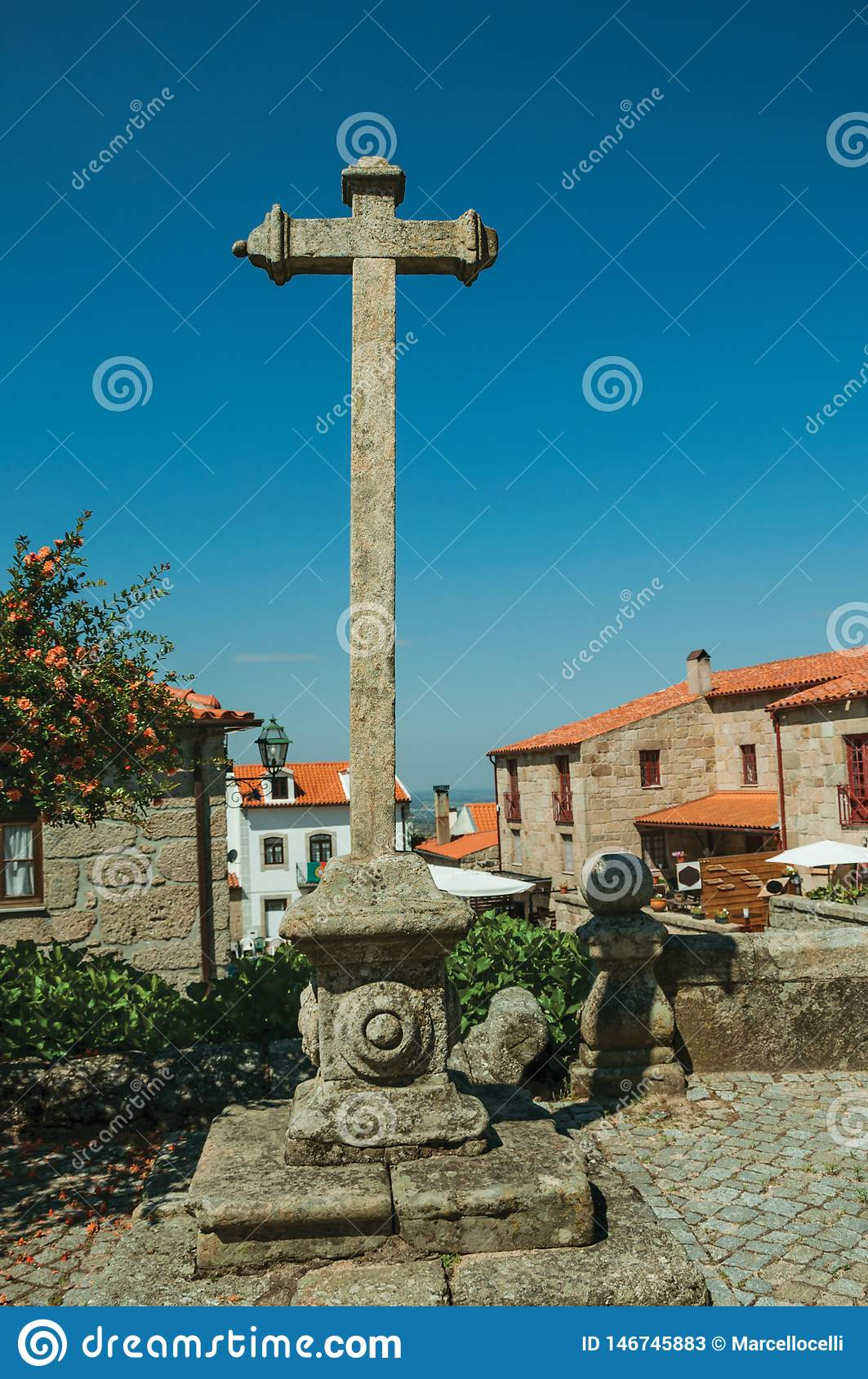 Cross shape pillory made of stone in courtyard and old houses