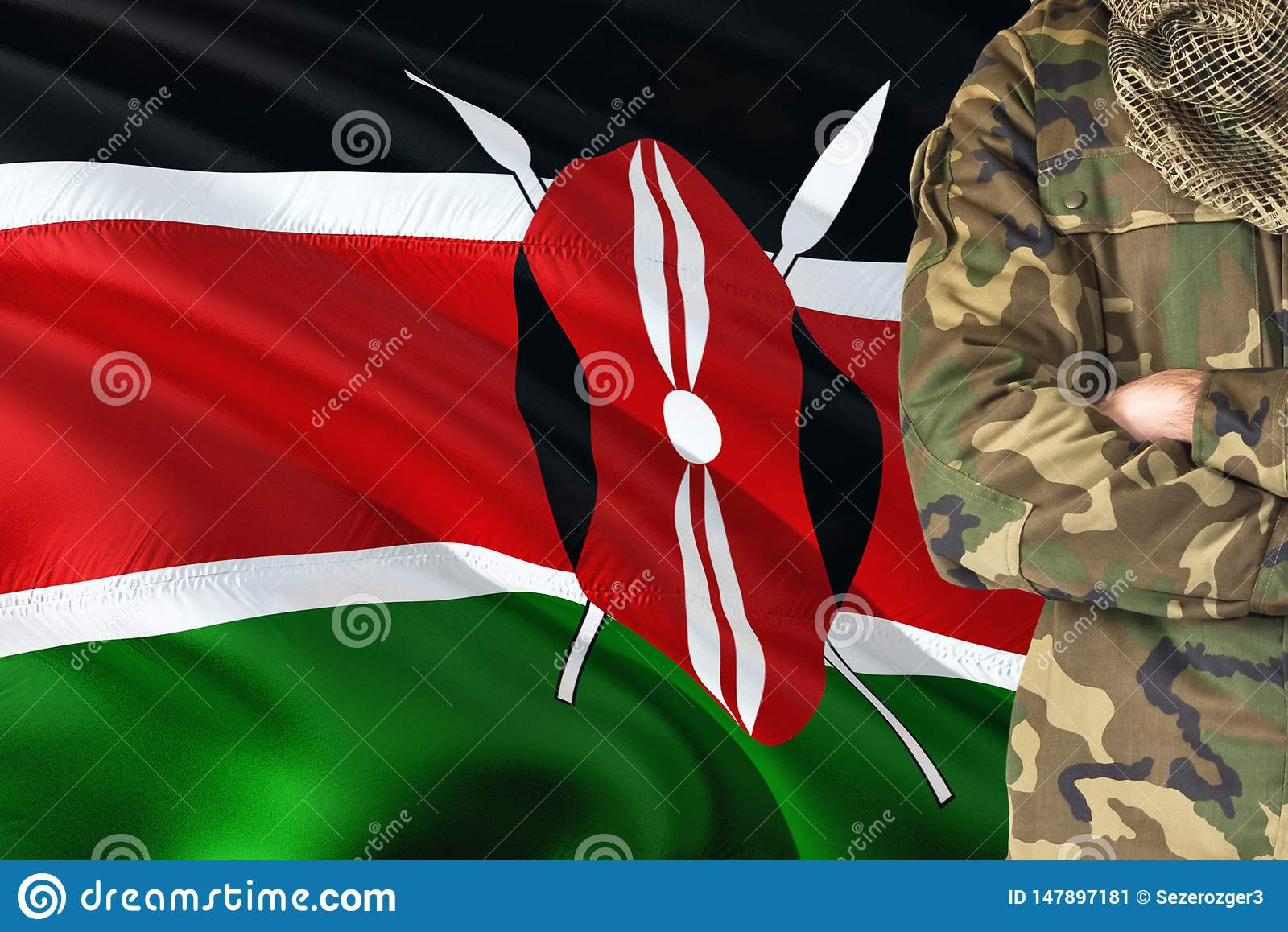 Crossed arms Kenyan soldier with national waving flag on background - Kenya Military theme