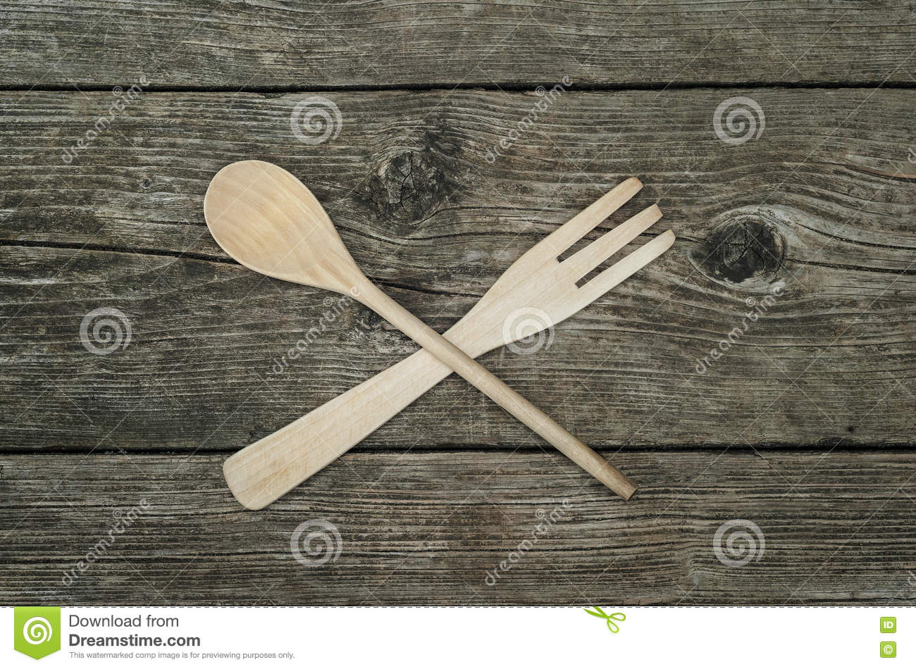 Crossed wooden fork and spoon on rustic background