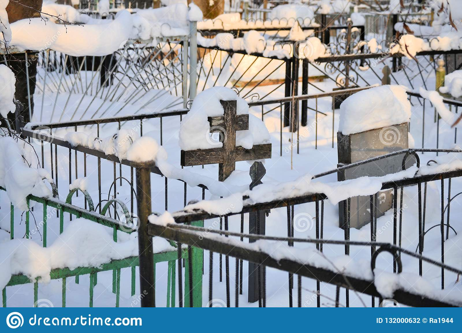 Crosses in a cemetery, monuments of the dead, a cemetery in winter, wreaths, artificial flowers. Russia
