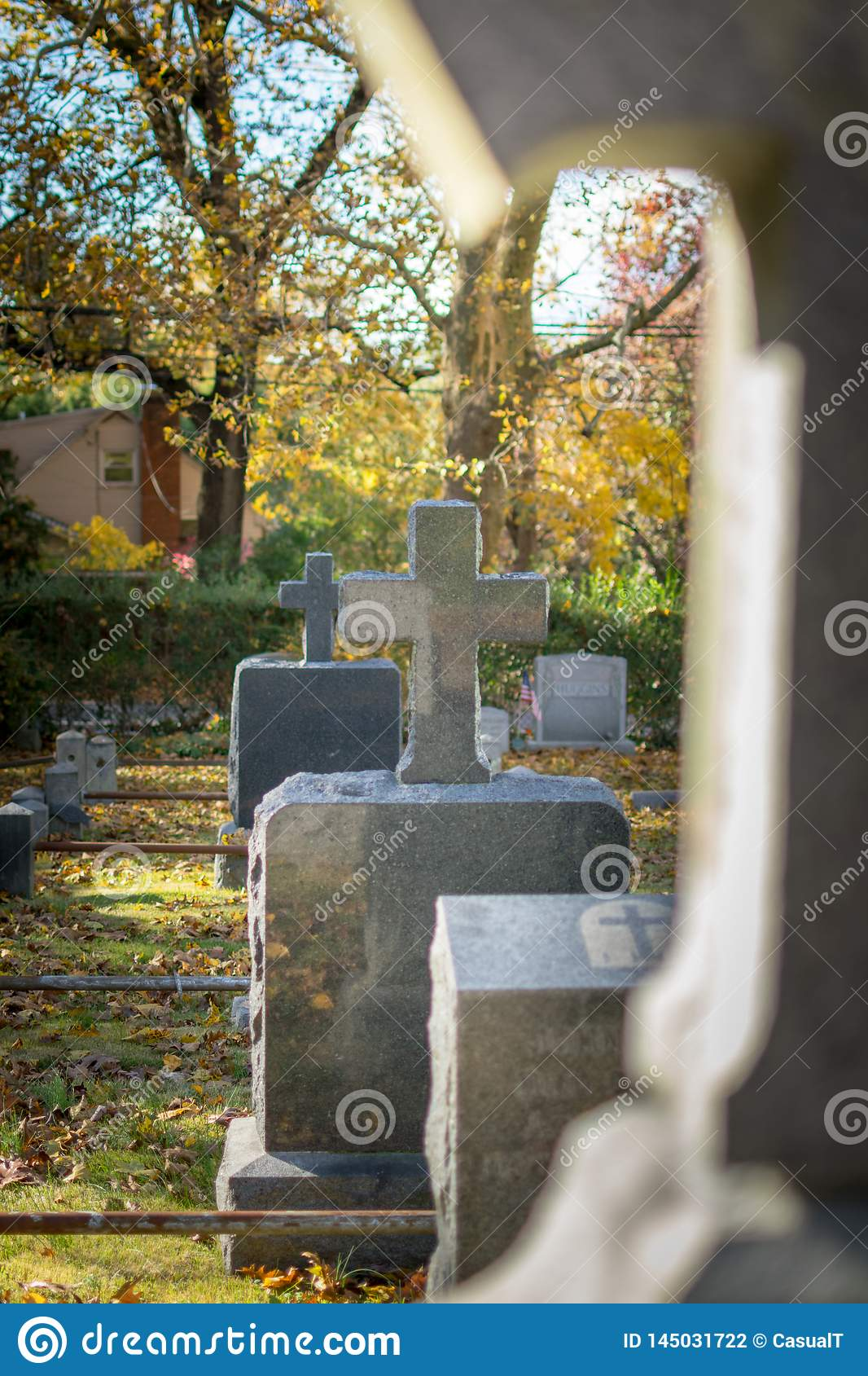 Crosses and gravestones among grass and fallen leaves, on an Autumn day at Sleepy Hollow Cemetery, Upstate New York, NY